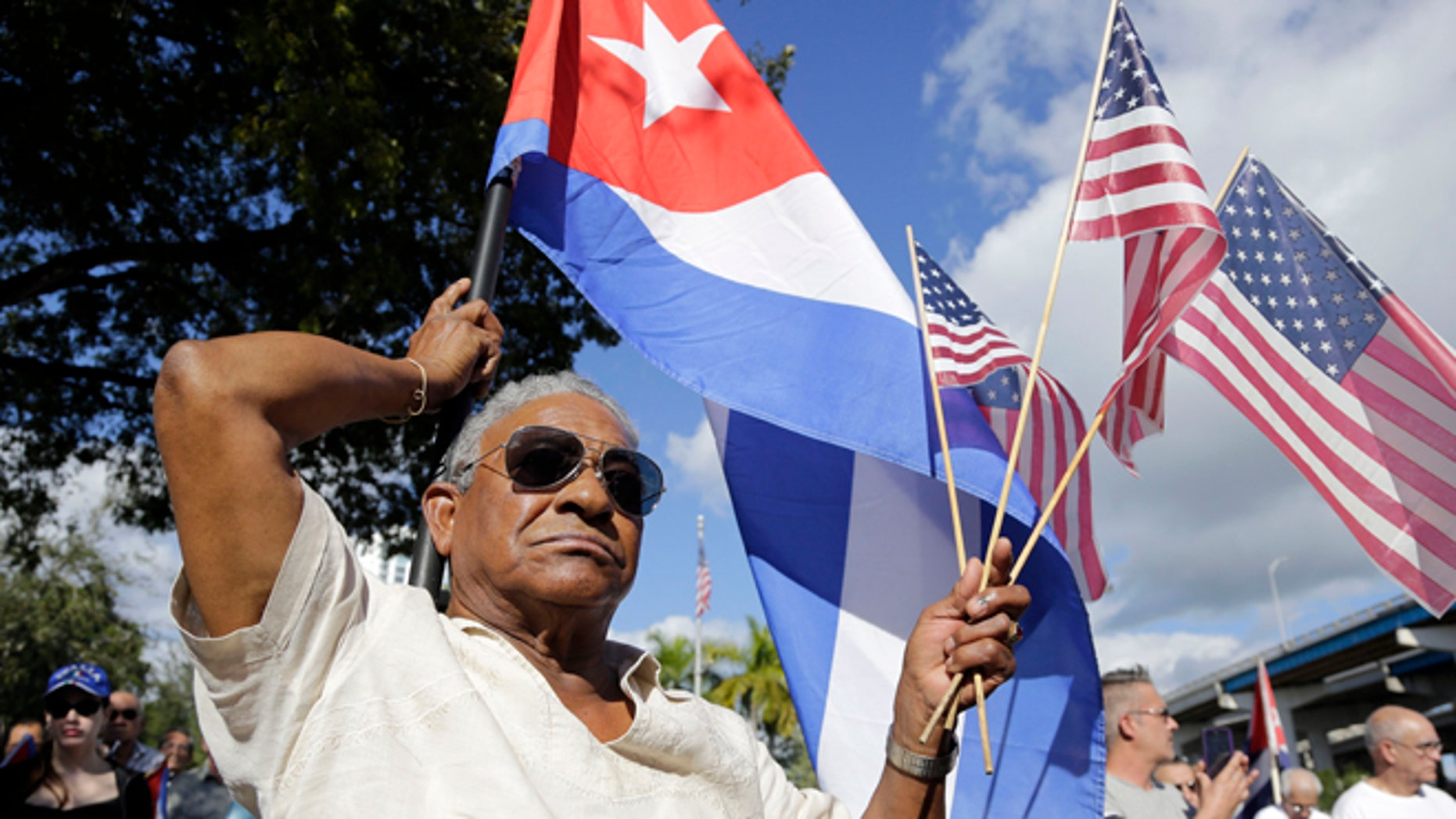 Evilio Ordonez holds Cuban and American flags during a protest against President Barack Obama's plan to normalize relations with Cuba, Saturday, Dec, 20, 2014, in the Little Havana neighborhood of Miami. Florida newspaper editors voted President Barack Obama's mid-December move to normalize relations with Cuba as one of the top stories of the year. (AP Photo/Lynne Sladky)