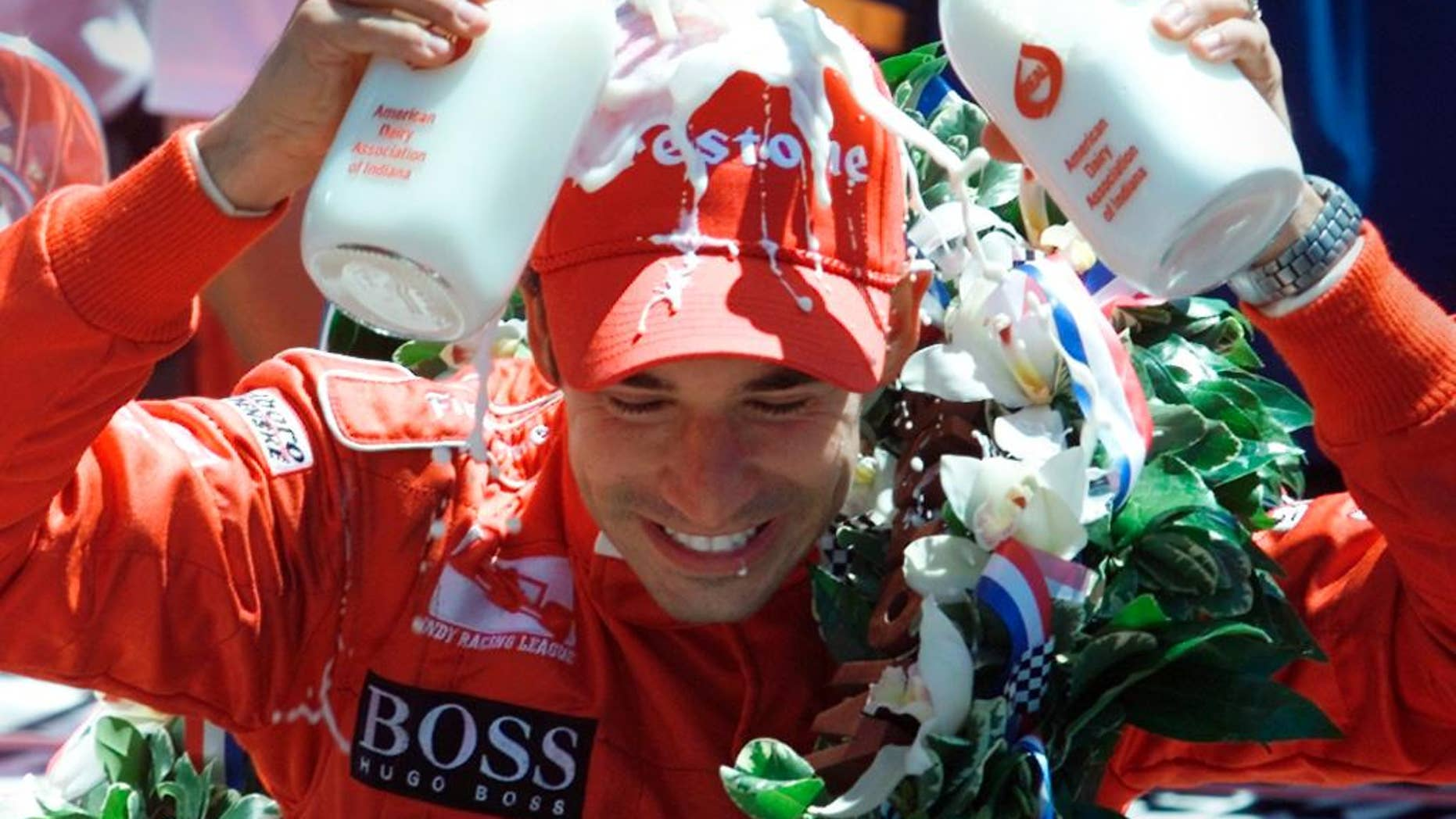 FILE - In this May 26, 2002, file photo, Indianapolis 500 champion Helio Castroneves of Brazil pours two bottles of milk onto his head after winning his second consecutive Indianapolis 500 auto race, in Indianapolis. (AP Photo/Michael Conroy, File)