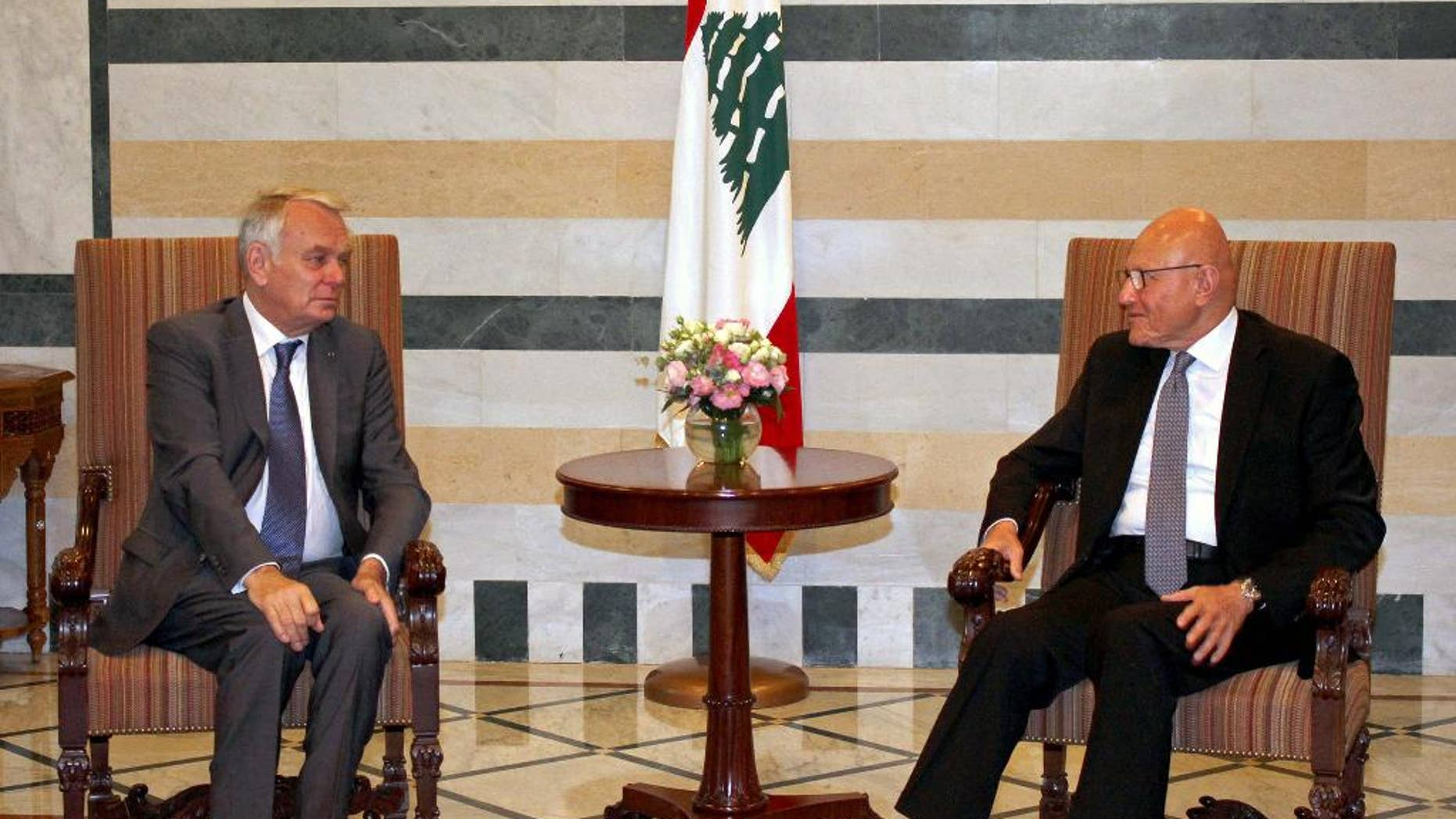 In this photo released by Lebanon's official government photographer Dalati Nohra, Lebanese Prime Minister Tammam Salam, right, meets with French Foreign Minister Jean-Marc Ayrault, left, at the government House, in Beirut, Lebanon, Tuesday, July 12, 2016. Ayrault said his country will do everything it can to help Lebanon emerge from its political stalemate. (Dalati Nohra via AP)