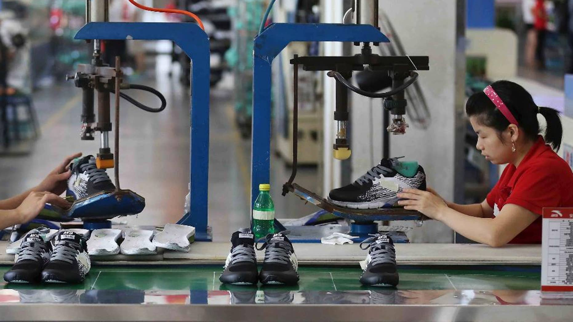 In this Wednesday, July 27, 2016 photo, workers assemble sneaker at a factory in Jinjiang city in southeast China's Fujian province. Two surveys show Chinese manufacturing activity in July was weak but better than some forecasters expected. A business magazine, Caixin, said Monday, Aug. 1, 2016 its purchasing managers index rose to 50.6 from June's 48.6 on a 100-point scale on which numbers above 50 show activity expanding. The China Federation of Logistics and Purchasing, an industry group, said its separate PMI edged down to 49.9 from June's 50. (Chinatopix Via AP)