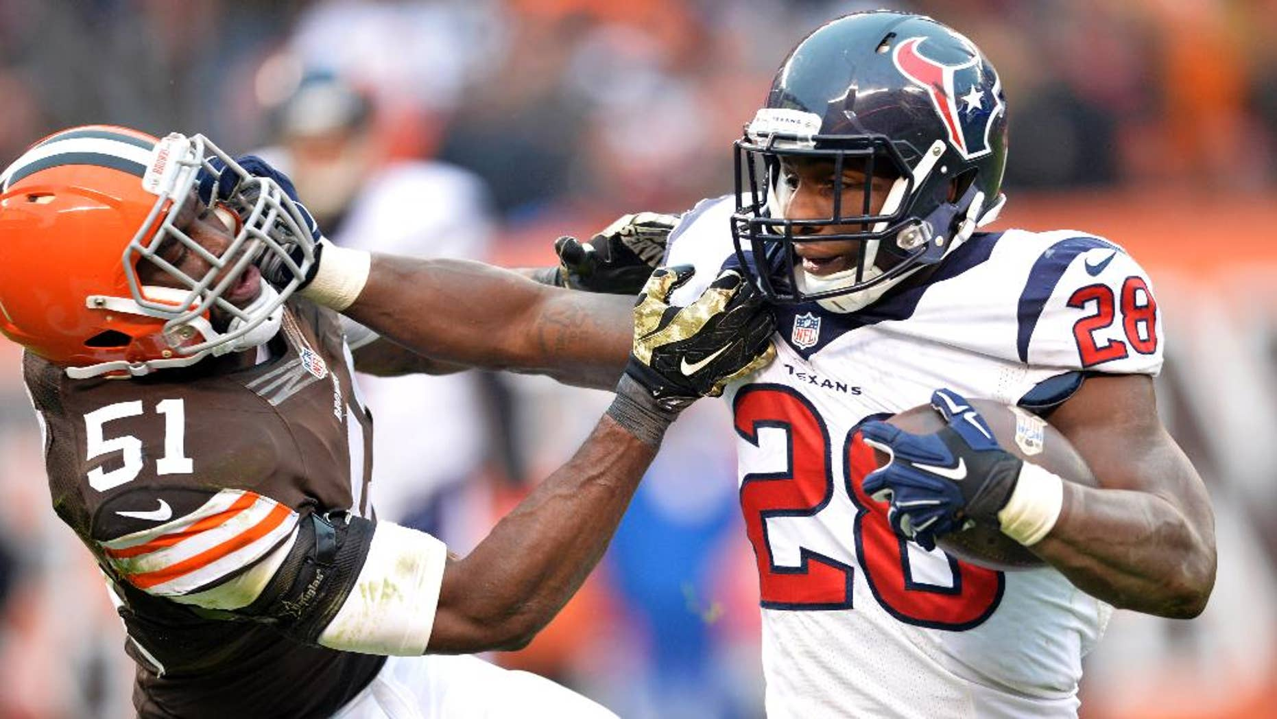 Houston Texans running back Alfred Blue (28) fights for yardage against Cleveland Browns outside linebacker Barkevious Mingo (51) in the fourth quarter of an NFL football game Sunday, Nov. 16, 2014, in Cleveland. (AP Photo/David Richard)
