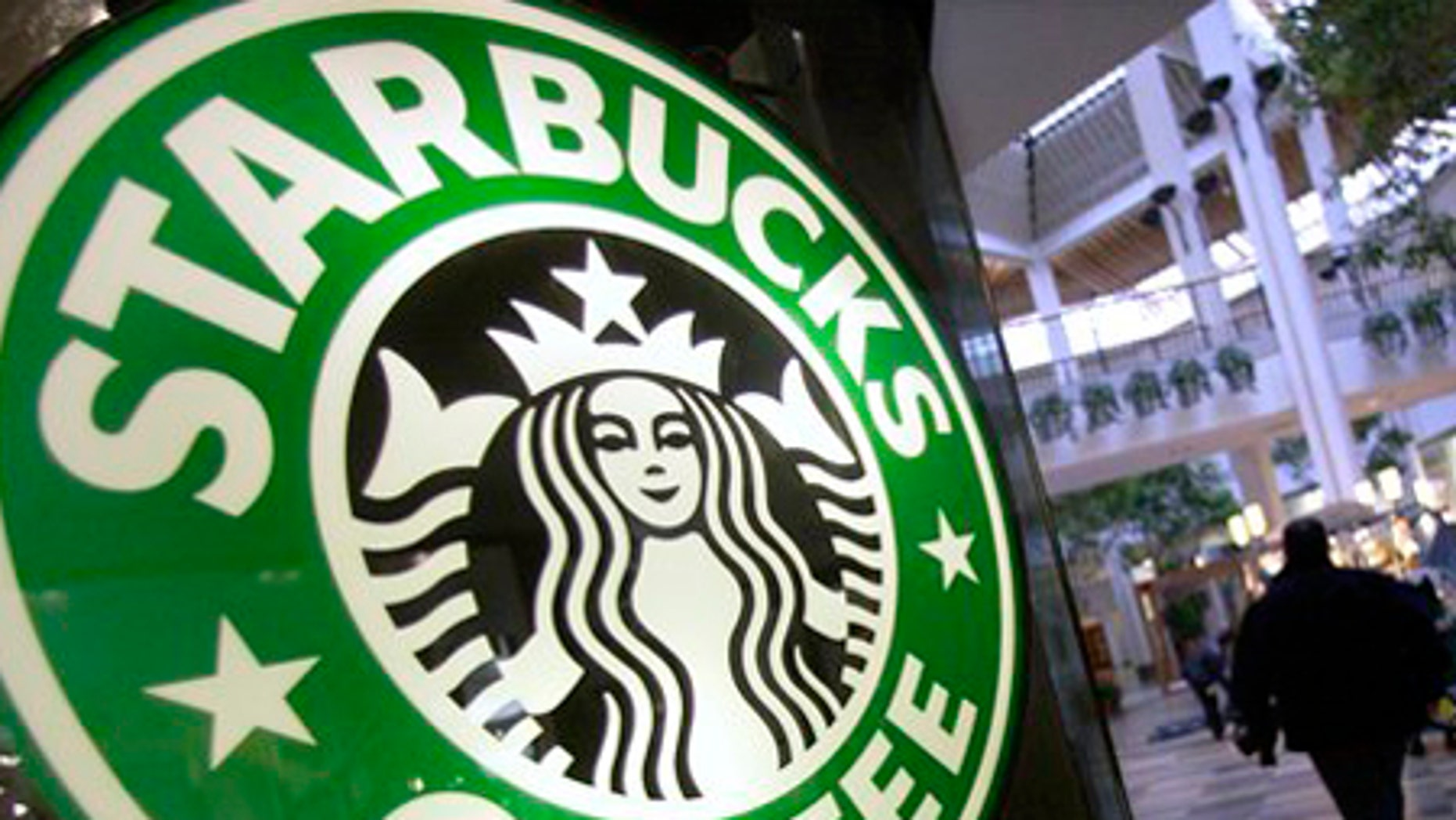 ** FILE ** In this Nov. 10, 2008 file photo, a man pulls a cart past a Starbucks store inside the Beachwood Mall in Beachwood, Ohio.  The allure of the value meal has long seduced penny-pinchers craving a cheeseburger. Now, as the dismal economy slurps up profits, Starbucks Corp. is hoping to find some sales salvation in its own value meal variety. (AP Photo/Amy Sancetta, file)