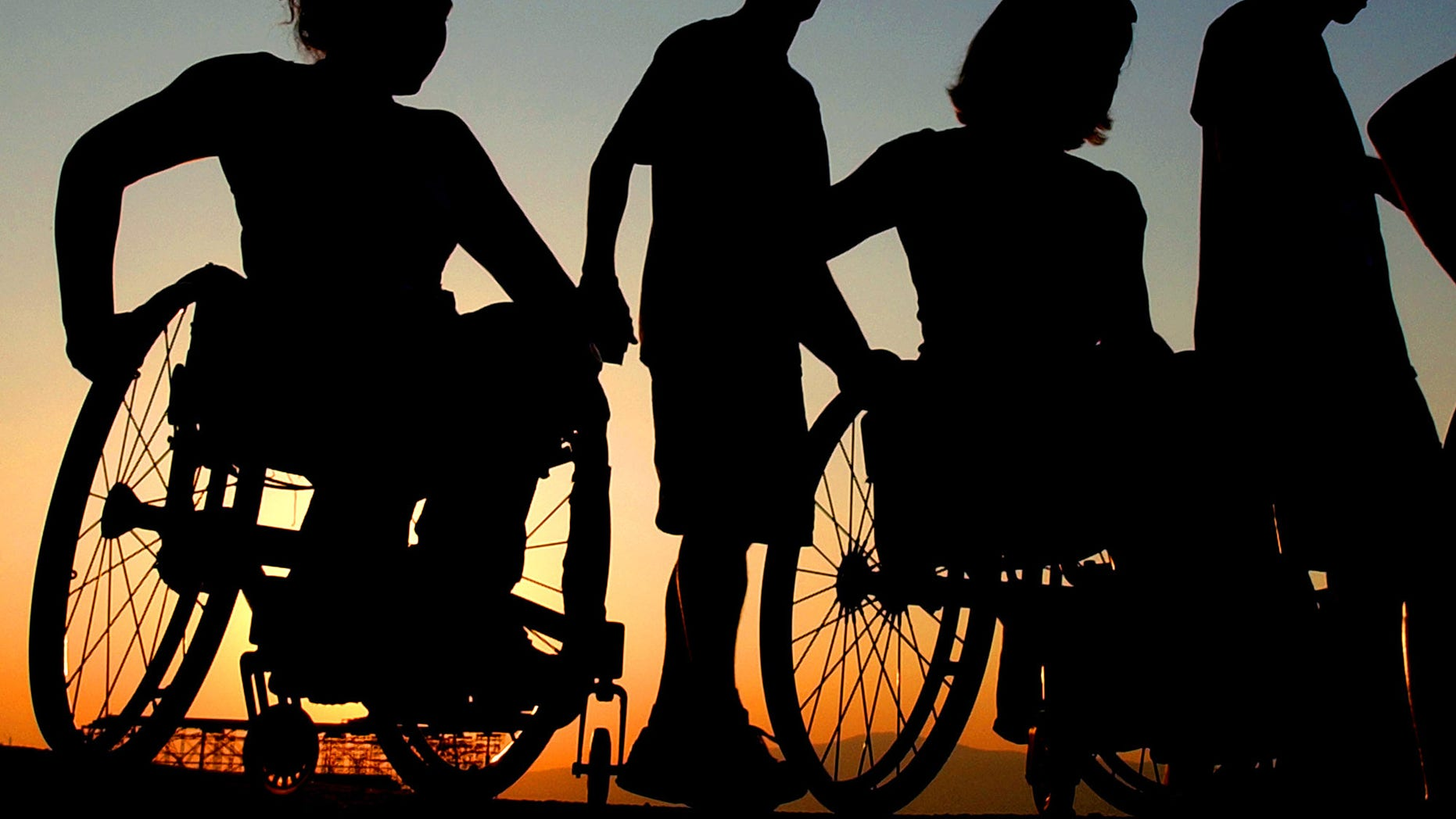 Members of the U.S. women's track and field Paralympic team, in wheelchairs, visit the Acropolis Hill with escorts, in Athens on Wednesday, Sept. 15, 2004. The Athens Paralympics start Friday. (AP Photo/Petros karadjias)