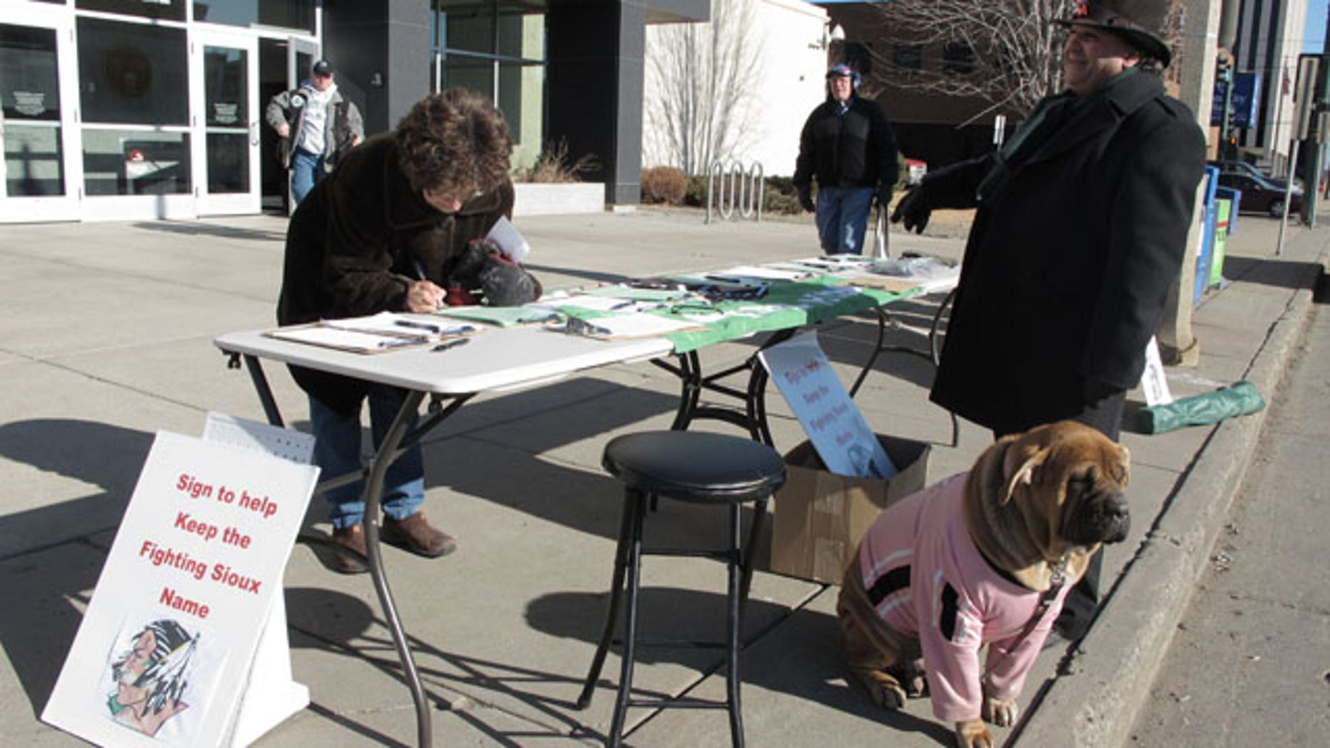 Feb. 7, 2012: Charles Tuttle, a backer of the University of North Dakota's Fighting Sioux nickname, watches as a woman signs petitions supporting the nickname in front of the federal courthouse in Bismarck, N.D.