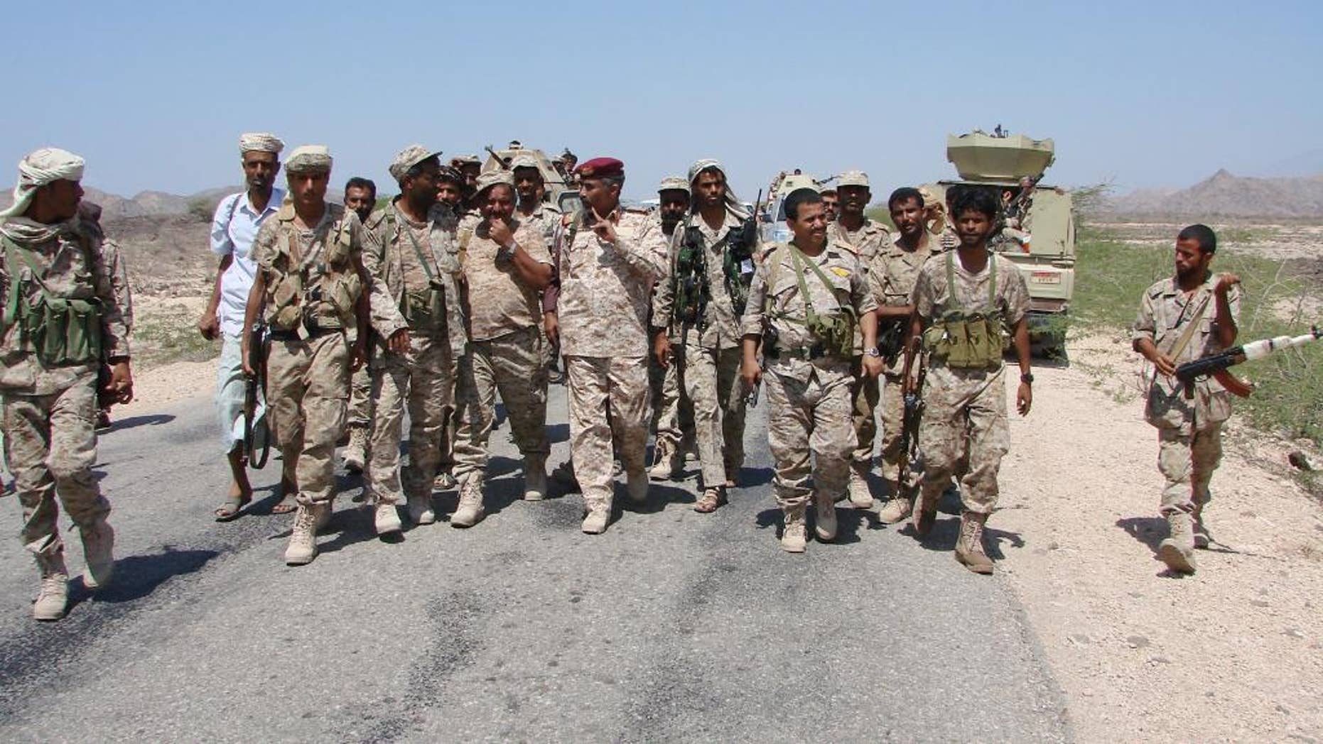 In this Friday, May 1, 2014, photo provided by Yemen's Defense Ministry, army officers and soldiers patrol a road during fighting with al-Qaida militants in Majala of the southern province of Abyan, Yemen. (AP Photo/Yemen's Defense Ministry)