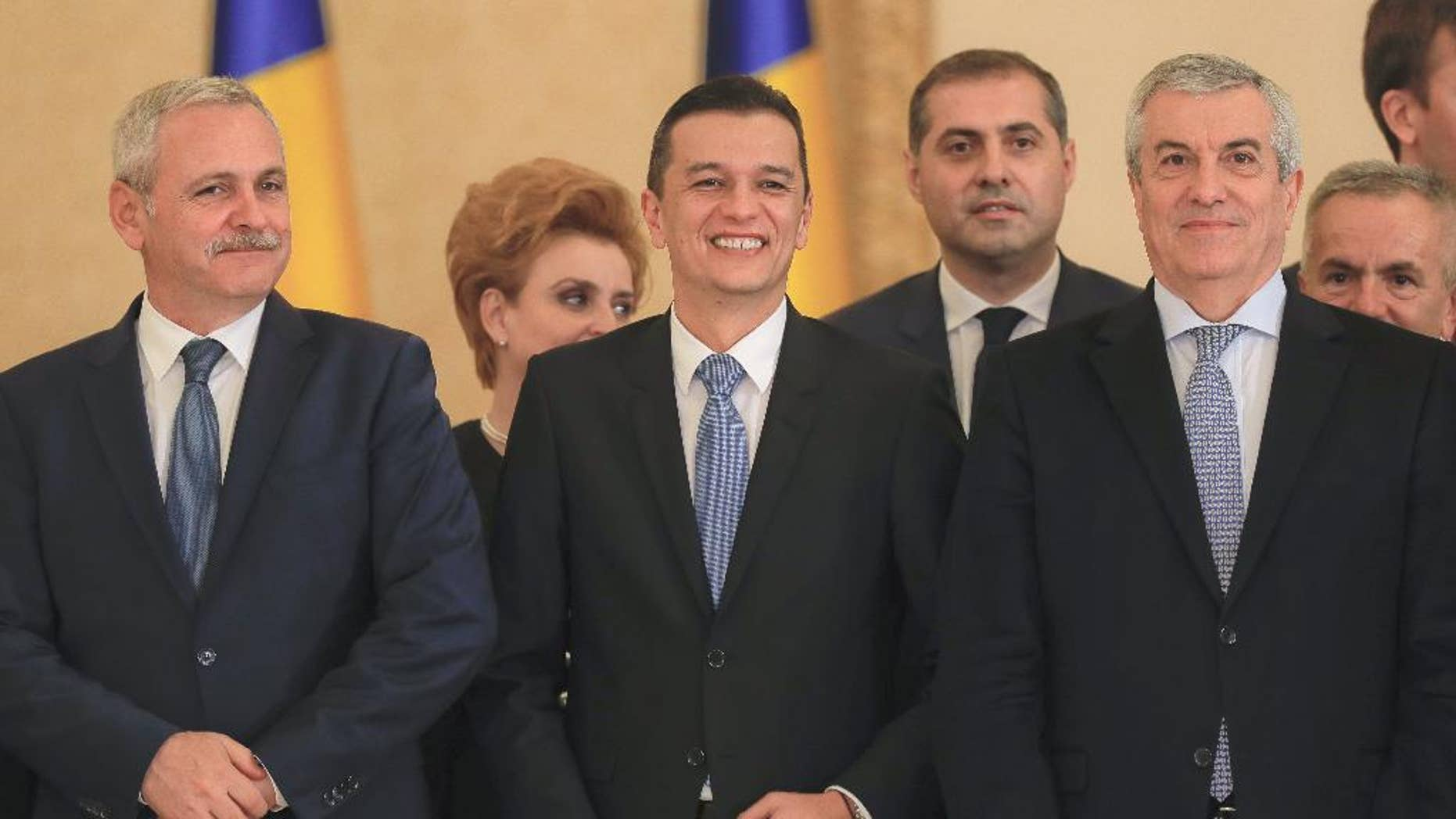 Romanian Prime Minister Sorin Grindeanu, center, smiles while standing between Liviu Dragnea, the leader of the Social Democratic party, left, and Calin Popescu Tariceanu, head of Romania's Senate, after the swearing in ceremony for his cabinet, in Bucharest, Romania, Wednesday, Jan. 4, 2017.  Iohannis swore in the new government shortly after it was voted in by parliament, urging it to guarantee an independent justice system and the rule of law, and strengthen its position within the European Union and NATO.(AP Photo/Vadim Ghirda)