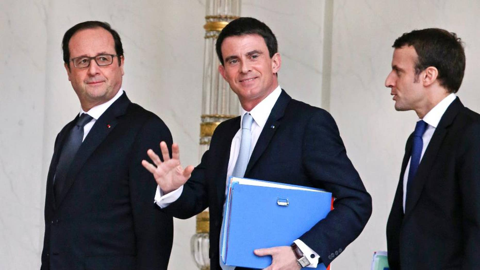 French Prime Minister Manuel Valls, center, waves to reporters as he walks in the lobby of the Elysee Palace with French President Francois Hollande, left, and Economy Minister Emmanuel Macron, right, in February 2015.