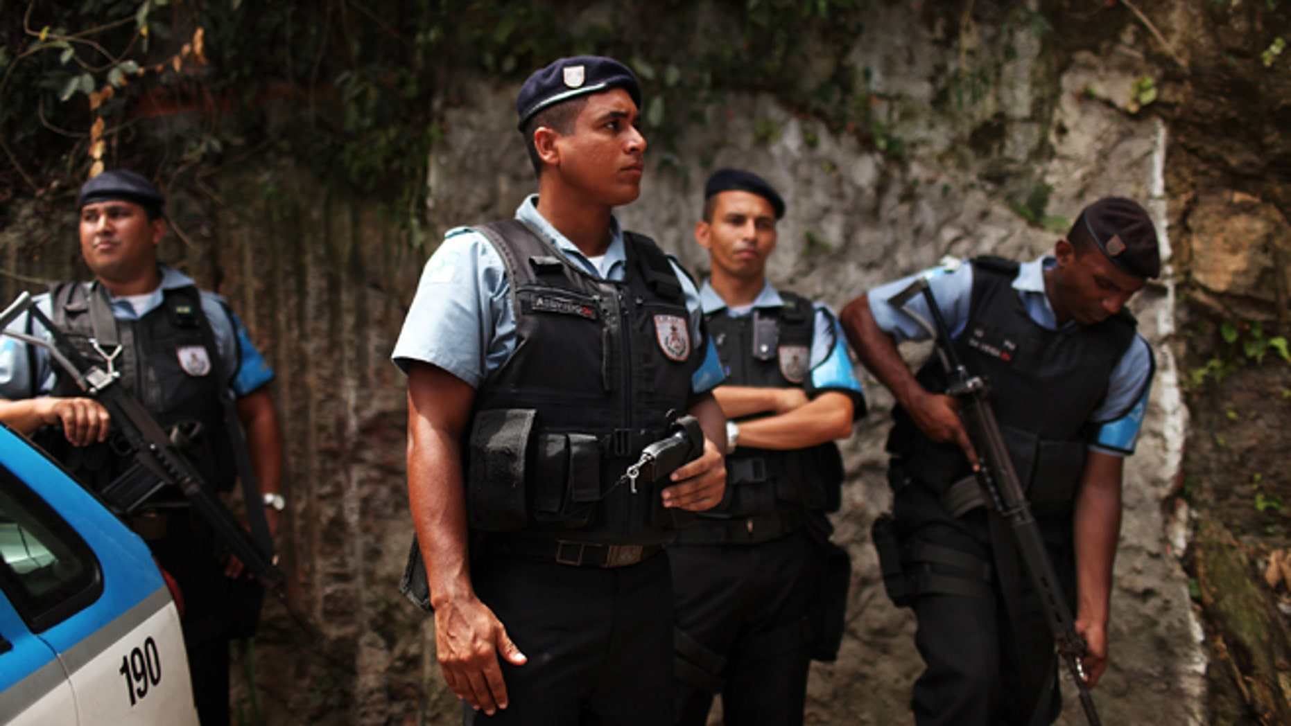 "RIO DE JANEIRO, BRAZIL - DECEMBER 03:  Police officers patrol the recently ""pacified"" Babilônia slum, or favela, on December 3, 2009 in Rio de Janeiro, Brazil. Babilônia is one of a number of Favelas in Rio where the police are attempting a softer touch by participating in community policing after they clear the area of drug gangs. It is believed that the police want to continue with these programs citywide ahead of the 2016 Olympic Games. As Brazil prepares to host the 2016 Summer Olympics international scrutiny is falling on Rio de Janeiro`s favelas where over 5,000 people were murdered  last year alone. In the last week violence in tourist areas has increased as drug gangs are increasingly reacting to an increased police presence in the favelas. In figures released Tuesday by the IBGE (Instituto Brasileiro de Geografia e Estatística) statistics agency it was found that an average of 68 young Brazilian men died violently each day between 1998 and 2008. These numbers included murder, traffic accidents and gang violence involving the police.  (Photo by Spencer Platt/Getty Images)"