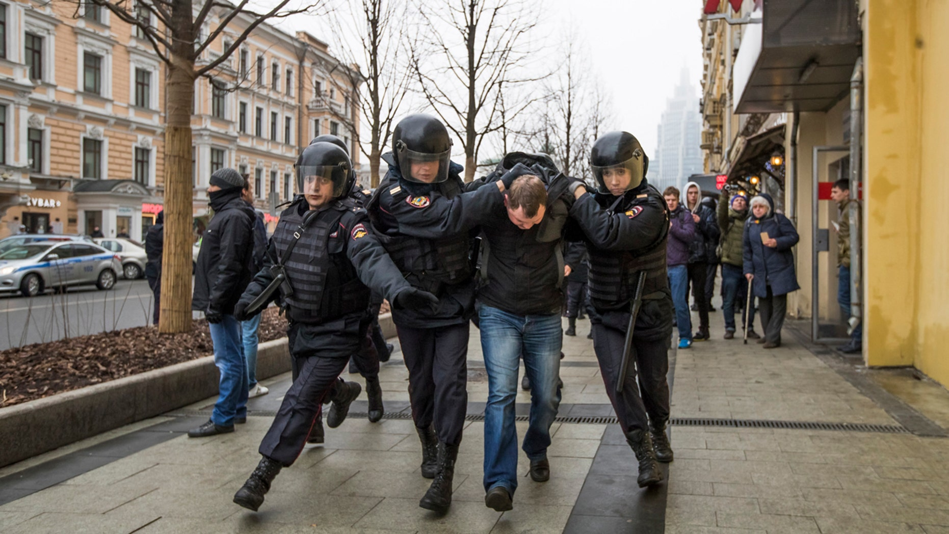Police officers detain a man in the main street in Moscow, Russia, Sunday, April 2, 2017.