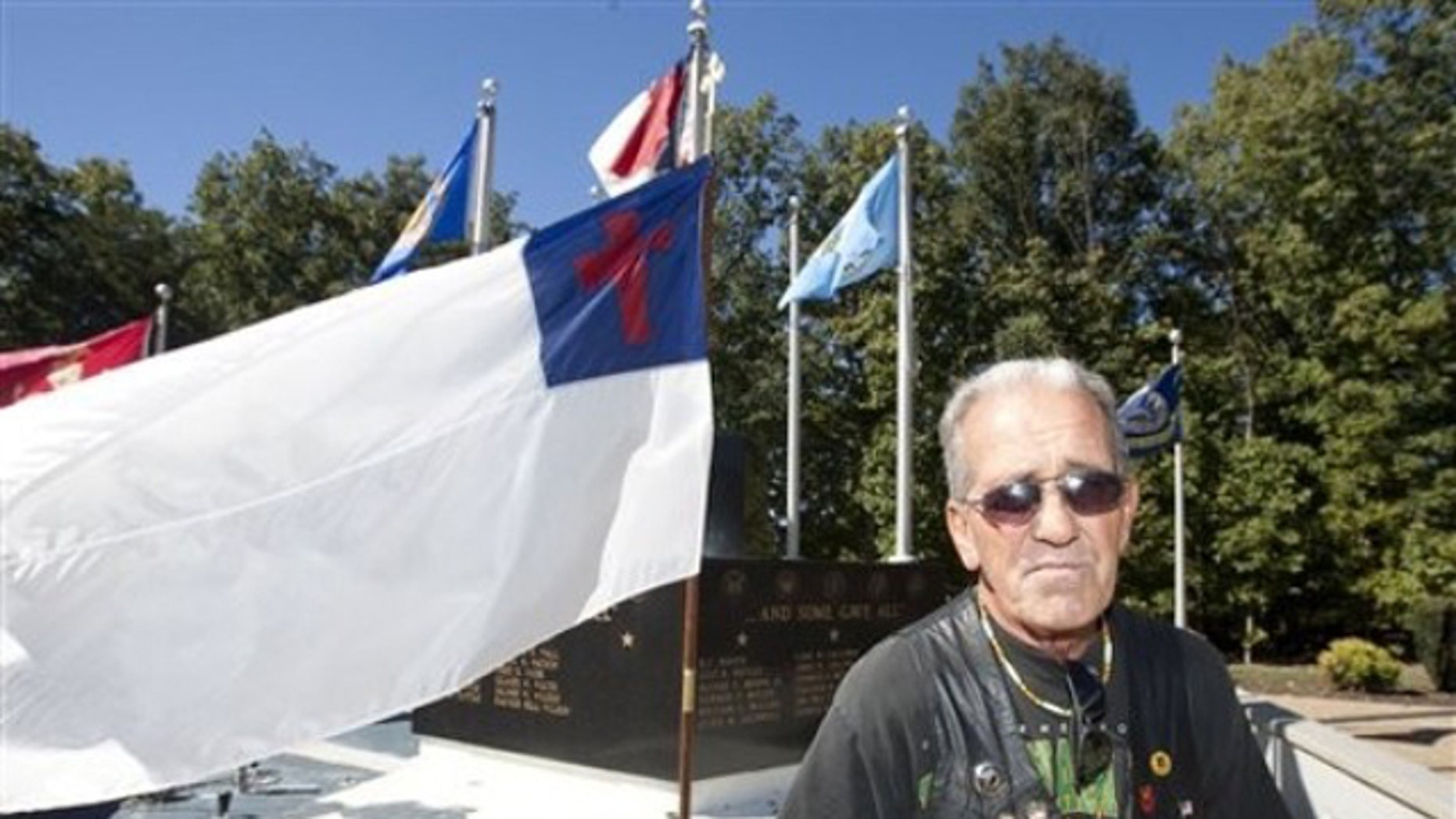 Oct. 16: Ray Martini, an Air Force Veteran, stands beside a Christian flag flying in front of the Veterans Memorial at Central Park in King, N.C. (AP).