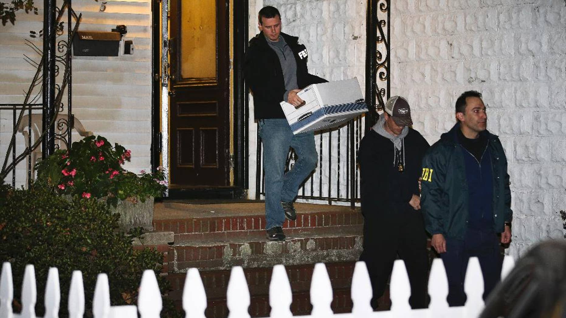 FILE - In a Thursday, Oct. 10, 2013 file photo, FBI agents remove evidence from the Brooklyn residence of Rabbi Mendel Epstein during an investigation, in New York. Several defendants, including Epstein and another rabbi, are accused by the FBI of plotting to kidnap and beat a man to force him to grant a religious divorce. Epstein's trial starts Tuesday, Feb. 17, 2015, in federal court in New Jersey. Several co-defendants have pleaded guilty and others will join him in court this week.  (AP Photo/John Minchillo, File)