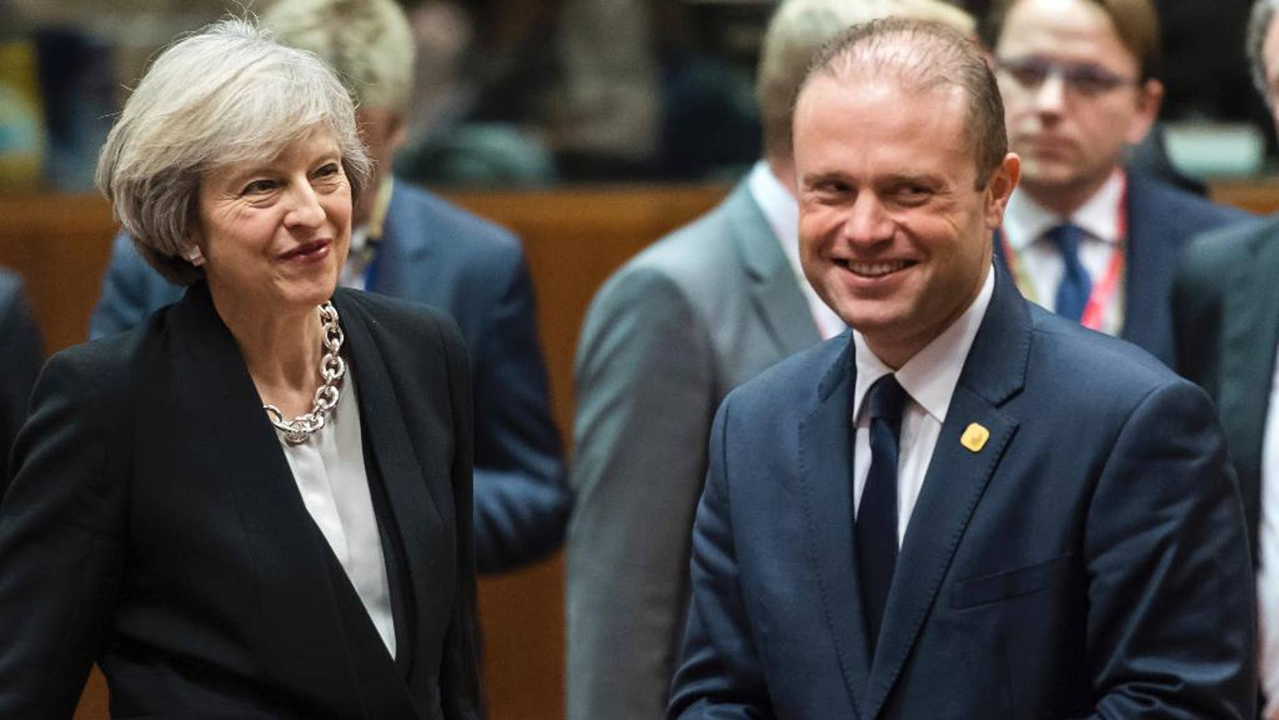 FILE - This is a Thursday, Dec. 15, 2016 file photo of British Prime Minister Theresa May, left, speaks with Malta's Prime Minister Joseph Muscat, during a round table meeting at an EU Summit in Brussels . Muscat the leader of the European Union's smallest nation warned Britain on Wednesday Jan. 11, 2016  that it can only lose by leaving the EU and that no member state is likely to break ranks and negotiate with London until it has departed. (AP Photo/Geert Vanden Wijngaert, File)