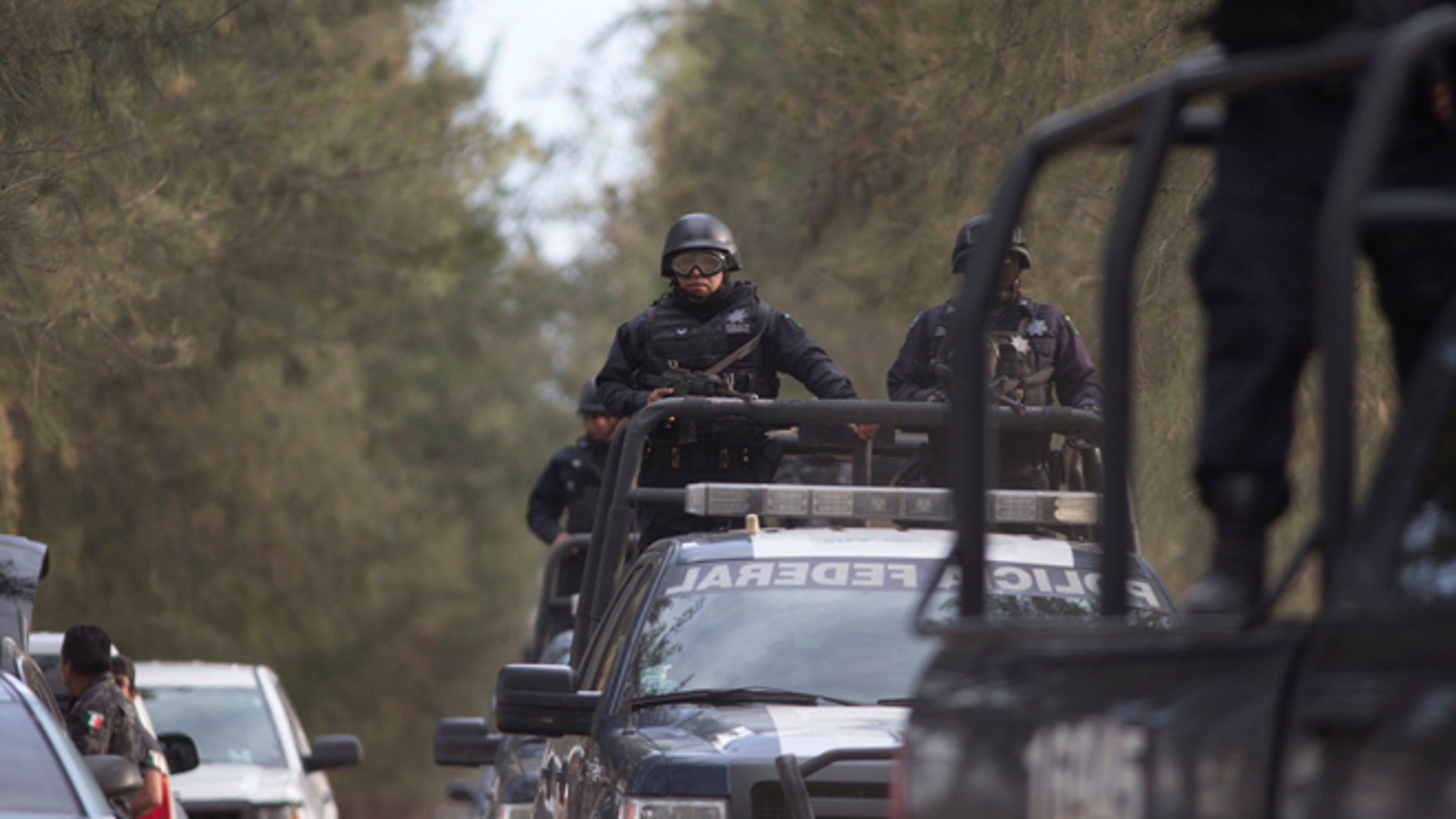 Mexican Federal Police stand guard near the entrance of Rancho del Sol, near Ecuanduero, in western Mexico, Friday, May 22, 2015. At least 43 people died Friday in what authorities described as a fierce, three-hour gunbattle between federal forces and suspected drug gang gunmen at the ranch. (AP Photo/Eduardo Verdugo)