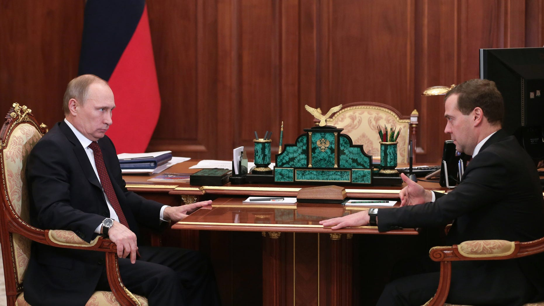 Russian President Vladimir Putin, left, speaks during a meeting with Premier Dmitry Medvedev in Moscow's Kremlin Monday, Dec. 30, 2013. Putin met with officials Monday to discuss the bombings in Volgograd. (AP Photo/RIA Novosti, Mikhail Metzel, Presidential Press Service)