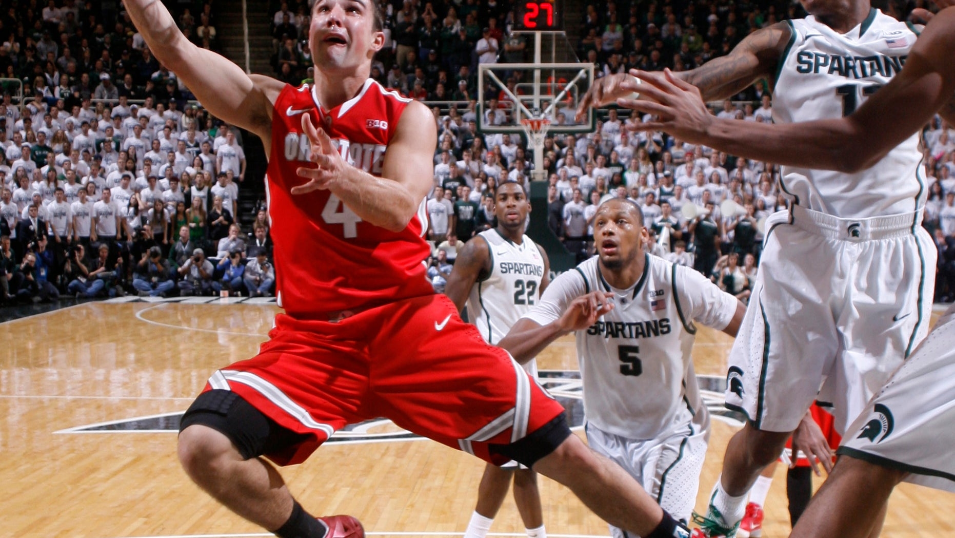 Ohio State's Aaron Craft (4) lays the ball up against Michigan State's Keith Appling, right, during overtime of an NCAA college basketball game, Tuesday, Jan. 7, 2014, in East Lansing, Mich. Michigan State won 72-68 in overtime. (AP Photo/Al Goldis)