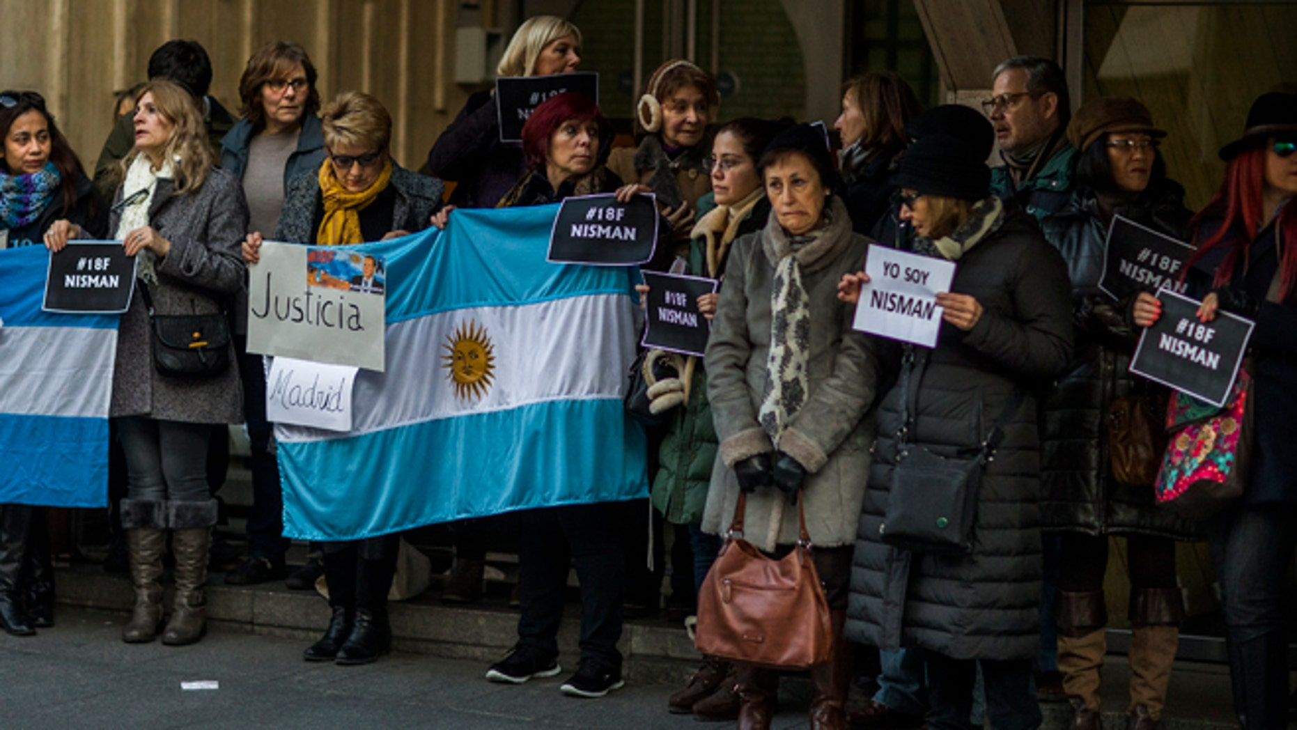"People hold signs reading in Spanish ""Justice"" and ""I am Nisman"" as they gather for justice and against impunity in the case of the mysterious death of late prosecutor Alberto Nisman outside the Argentinean Embassy in Madrid, Spain, Wednesday, Feb. 18, 2015. Nisman was scheduled to appear before Congress the day after he was found dead in his apartment on Jan. 18, to detail his allegations that President Cristina Fernandez had conspired to protect some of the Iranian suspects in the 1994 bombing of a Jewish center. (AP Photo/Andres Kudacki)"