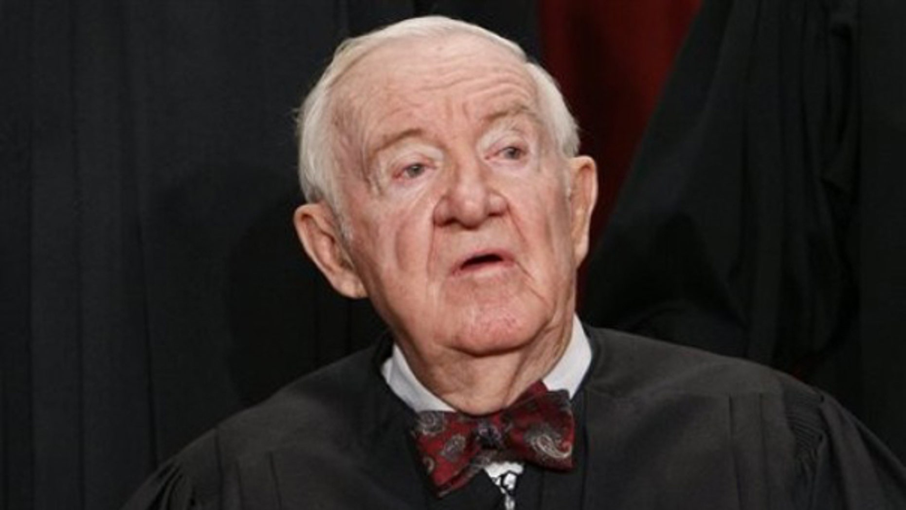 In this Sept. 29, 2009, file photo Associate Justice John Paul Stevens sits for a group photograph at the Supreme Court in Washington.