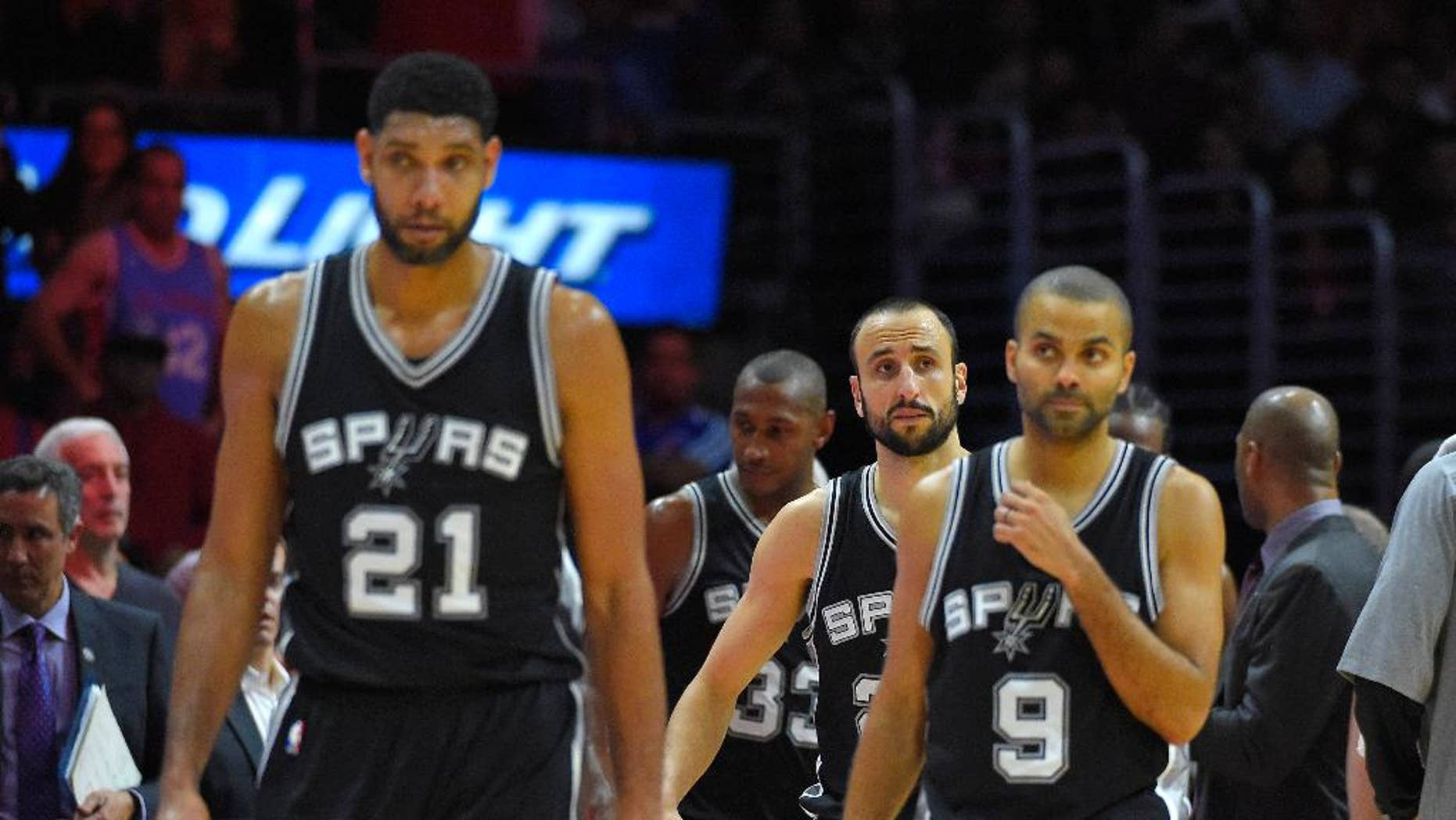 San Antonio Spurs forward Tim Duncan, left, guard Manu Ginobili, center, of Argentina, and guard Tony Parker, of France, look on during the second half of an NBA basketball game against the Los Angeles Clippers, Monday, Nov. 10, 2014, in Los Angeles.  The Spurs won 89-85. (AP Photo/Mark J. Terrill)