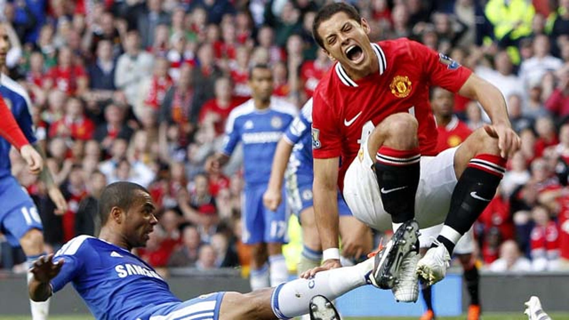 In this photo taken Sunday Sept. 18, 2011, Manchester United's Javier Hernandez reacts during a tough challenge from Chelsea's Ashley Cole, left, during the English Premier League soccer match at Old Trafford, Manchester. Hernandez limped off in the second half after the challenge by Cole. (AP Photo/Peter Byrne, PA) UNITED KINGDOM OUT