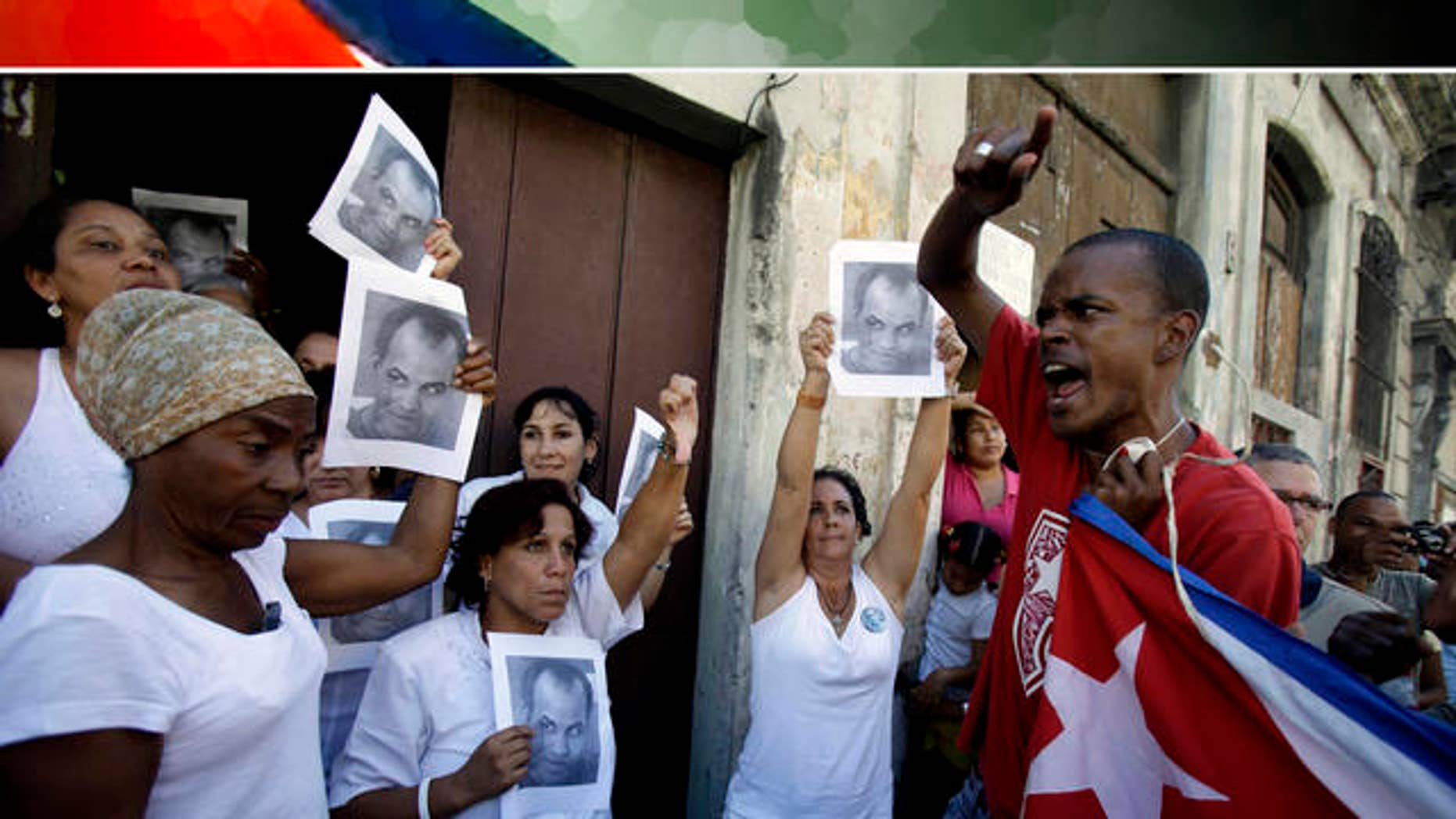 A government supporter, right, chants revolutionary slogans as members of dissident group Ladies in White hold up images of late dissident Orlando Zapata Tamayo on the first anniversary of his death in Havana, Cuba, Wednesday Feb. 23, 2011. Ladies in White is a group of relatives of Cuban dissidents who were or are still imprisoned.  (AP Photo/Javier Galeano)