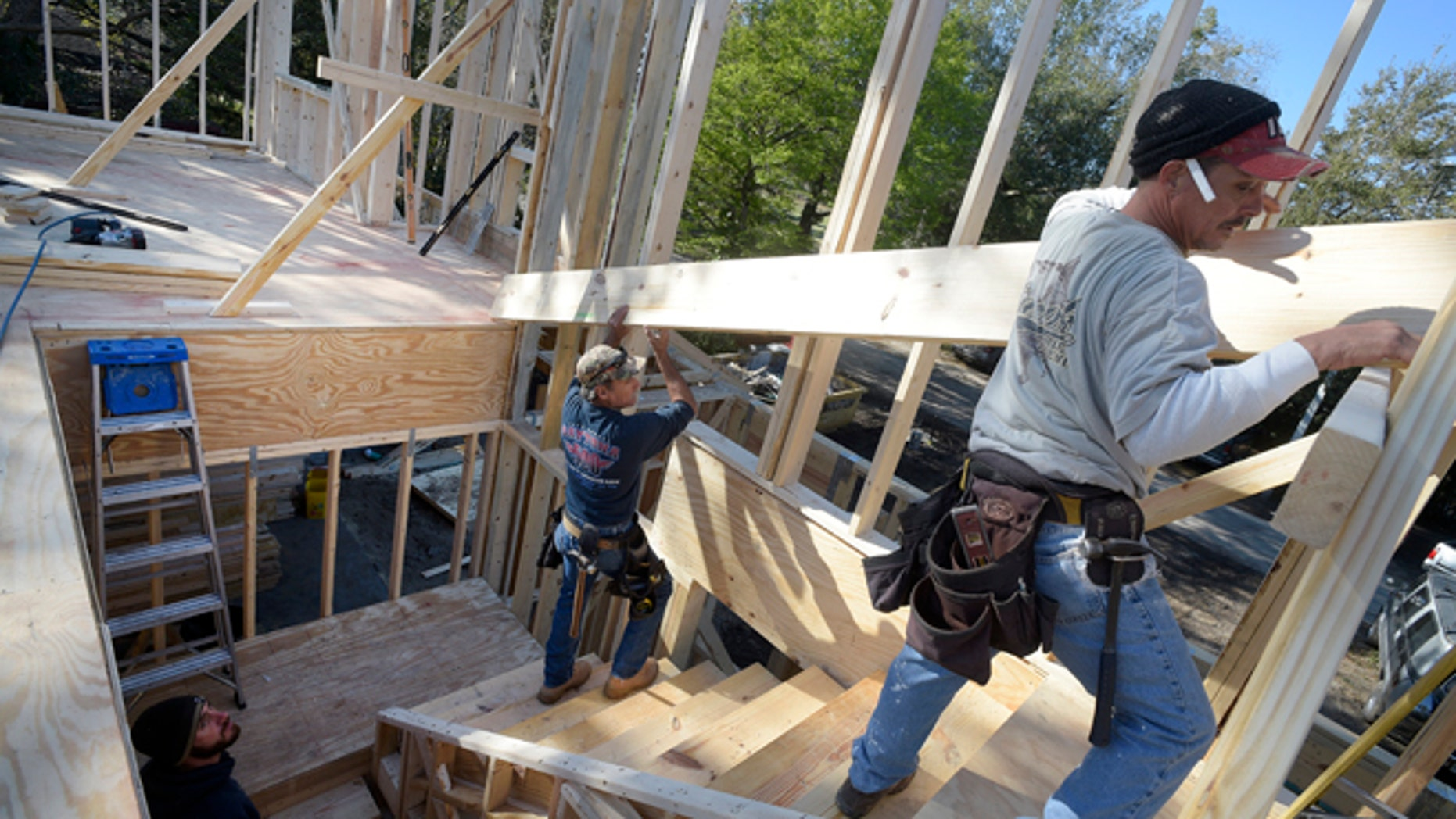 In this Feb. 13, 2015 photo, construction workers James Gibson, left, David Rager, center, and Shawn White frame the second floor of a two-story custom home being built in Orlando, Fla. As construction jobs return in some regions, competition for skilled labor is heating up.(AP Photo/Phelan M. Ebenhack)