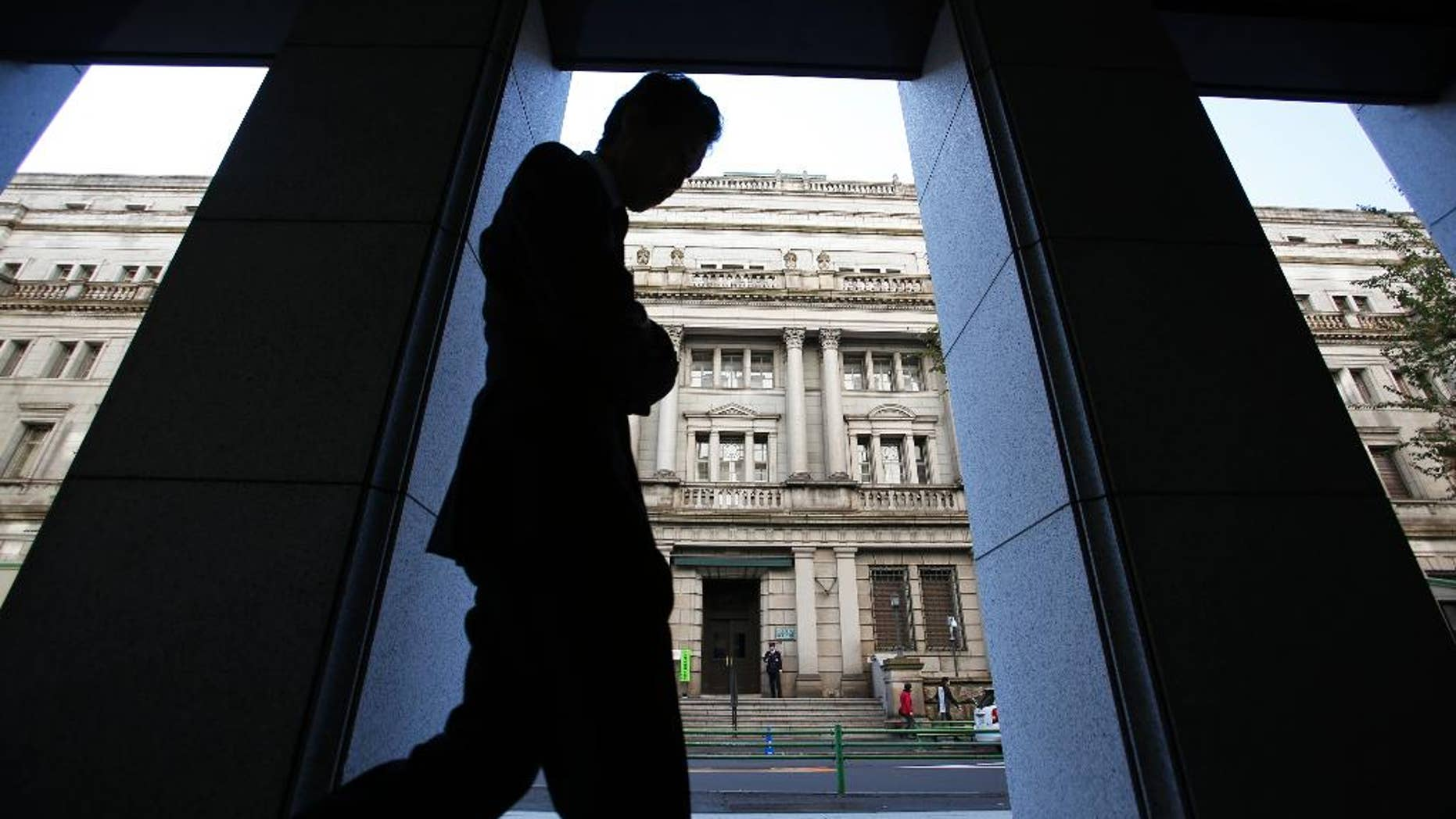 FILE - In this Nov. 19, 2014 file photo, a man walks in front of the Bank of Japan headquarters in Tokyo. Japan's latest data show the economy grew at a real annualized rate of 1.5 percent in October-December, slower than earlier reported but still reaffirming an end to recession. (AP Photo/Shizuo Kambayashi, File)