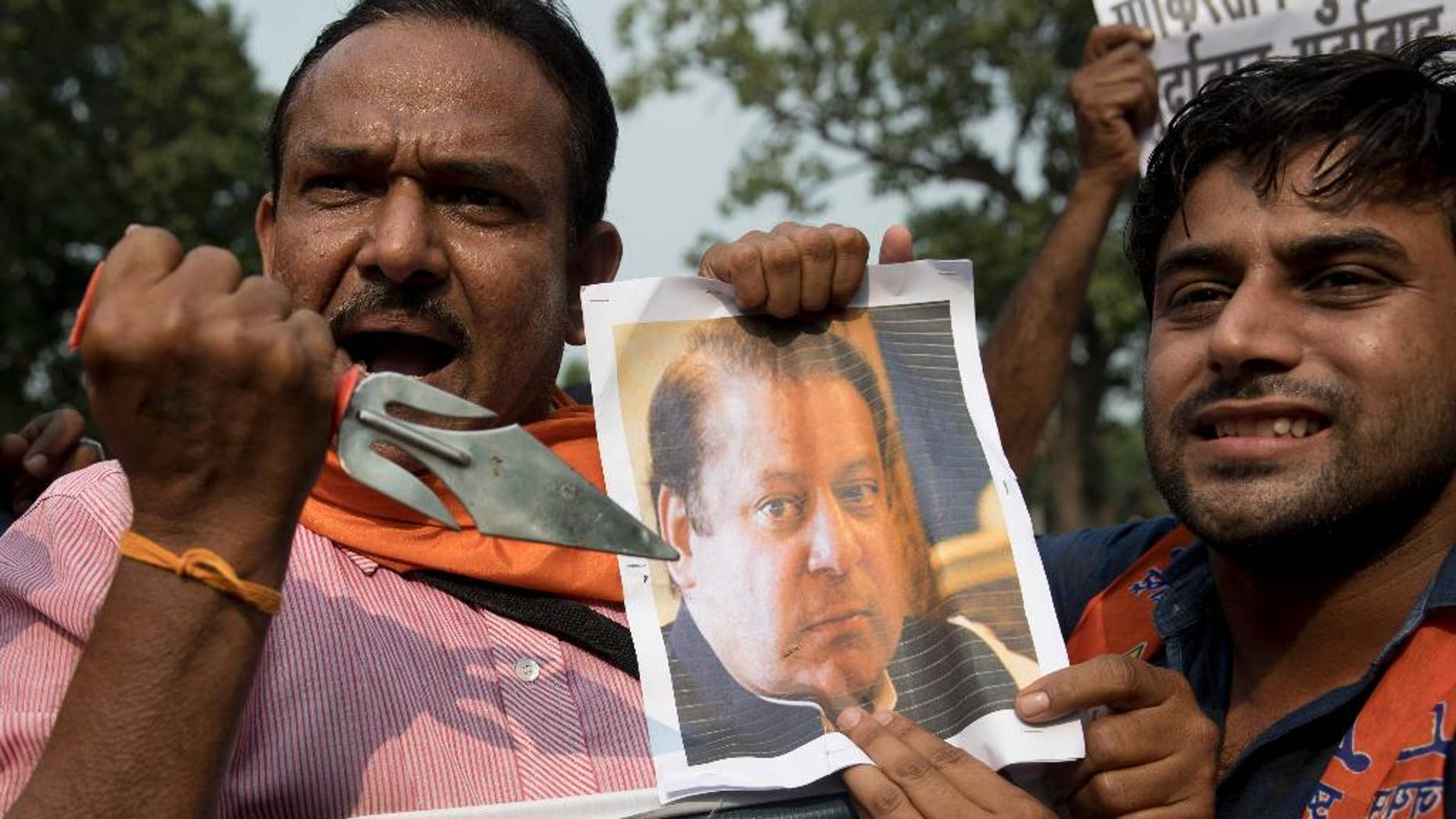 An activist of Hindu nationalist Shiv Sena party points a trident to a photograph of Pakistan Prime Minister Nawaz Sharif as they protest against Sunday's attack at an Indian army base in Kashmir, New Delhi, India, Monday, Sept. 19, 2016. India accuses Pakistan of training the militants in its territory, then helping them to infiltrate into the Indian side. Islamabad denies the charge, saying it only gives political and diplomatic support to the rebels. (AP Photo/Tsering Topgyal)