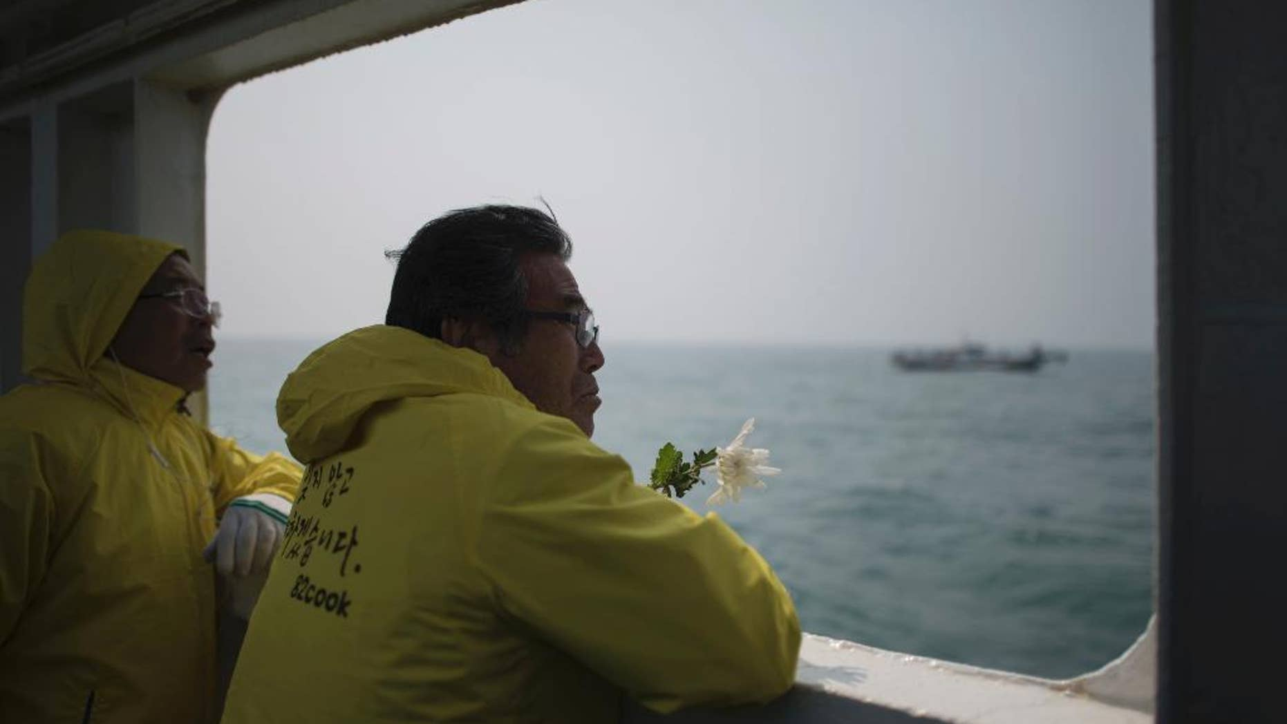 FILE - In this April 15, 2015, file photo, a relative of a victim of the ferry Sewol disaster watch the waters with flowers on the deck of a boat during a visit to the site of the sunken ferry, off the coast of South Korea's southern island of Jindo.  It took divers in South Korea more than three agonizing days just to enter the ferry Sewol after it sank on April 16, 2014. (Ed Jones/Pool Photo via AP, File)