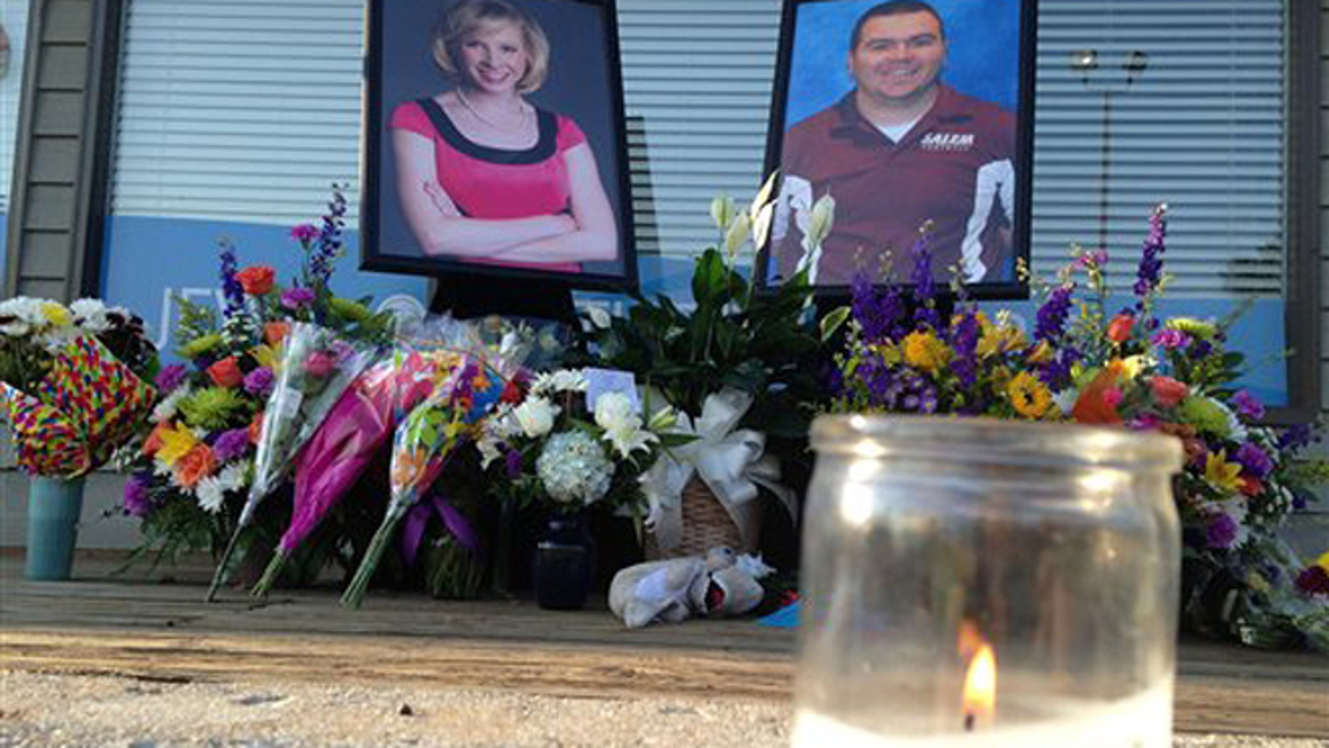 Aug. 28, 2015: A candle burns in front of a memorial for two slain journalists at Bridgewater Plaza in Moneta, Va.. The shopping center where the two were killed during a live television broadcast was reopening Friday for the first time since the shootings.