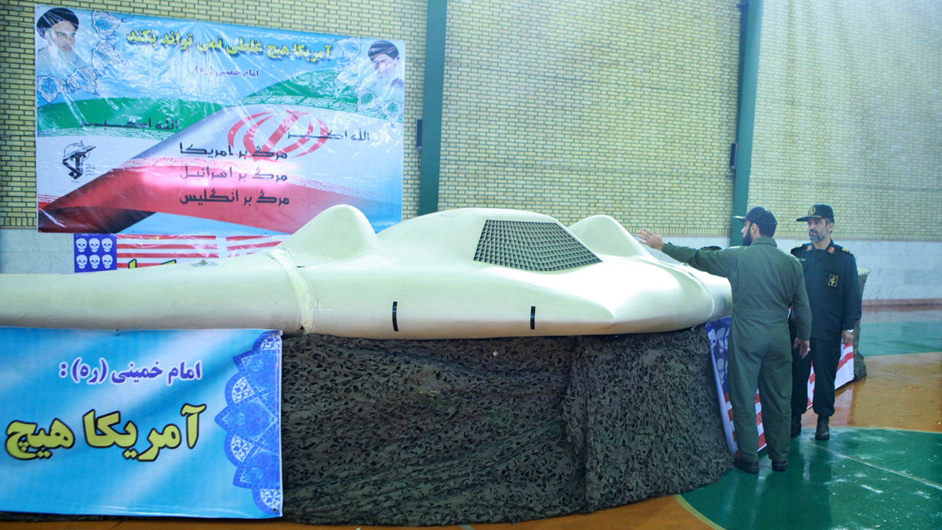 Dec. 8, 2011: This file photo released by the Iranian Revolutionary Guards, claims to show US RQ-170 Sentinel drone which Tehran says its forces downed earlier this week, as the chief of the aerospace division of Iran'ss Revolutionary Guards, Gen. Amir Ali Hajizadeh, right, listens to an unidentified colonel, in an undisclosed location, Iran.