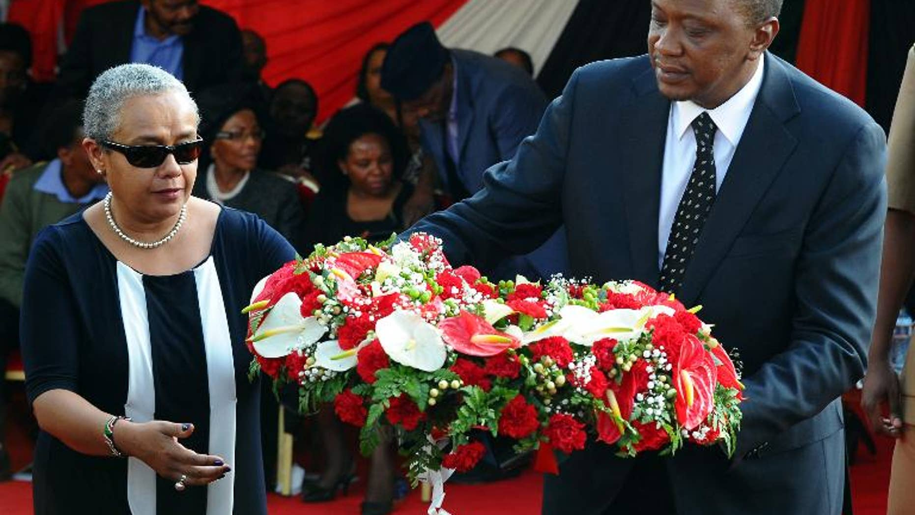 Kenyan President Uhuru Kenyatta and his wife Margaret lay a wreath of flowers during the funeral service of his nephew Mbugua Mwangi and his fiancee Rosemary Wahito in Nairobi on September 27, 2013
