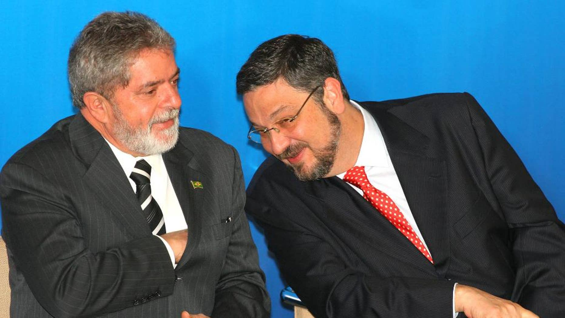 FILE - In this June 15, 2005 file photo, Brazil's President Luiz Inacio Lula da Silva, left, speaks with his Economy Minister Antonio Palocci during a ceremony at the presidential palace in Brasilia, Brazil.  Palocci was arrested, police said on Monday, Sept. 26, 2016, the latest detention in connection with a wide-ranging investigation into a kickback scheme in state oil company Petrobras. This month investigators charged Lula with money laundering and corruption.  (AP Photo/Eraldo Peres, File)