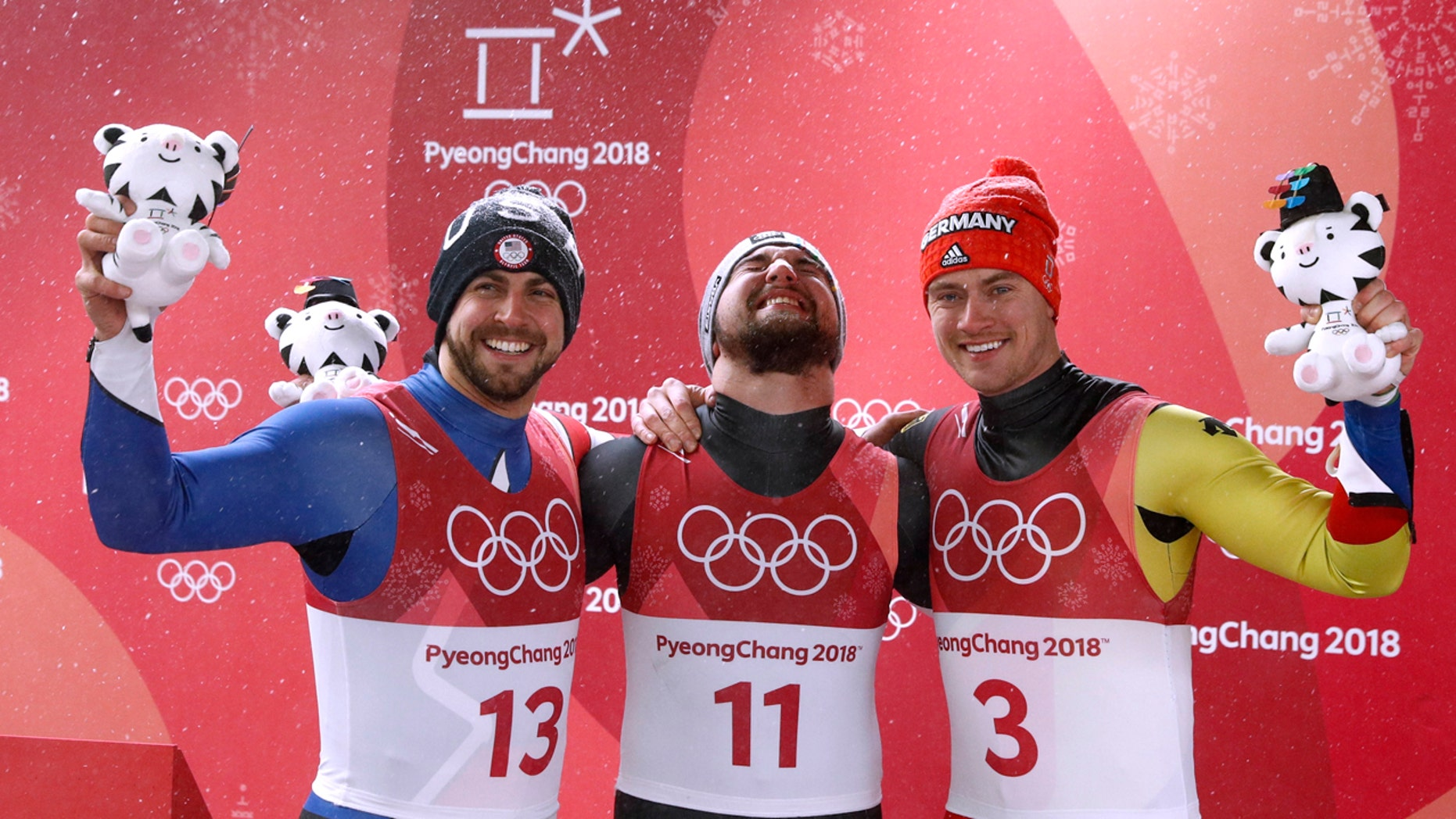 David Gleirscher of Austria, center, celebrates his men's singles luge win with 2nd-place Chris Mazdzer of the U.S. and 3rd-place Johannes Ludwig of Germany.