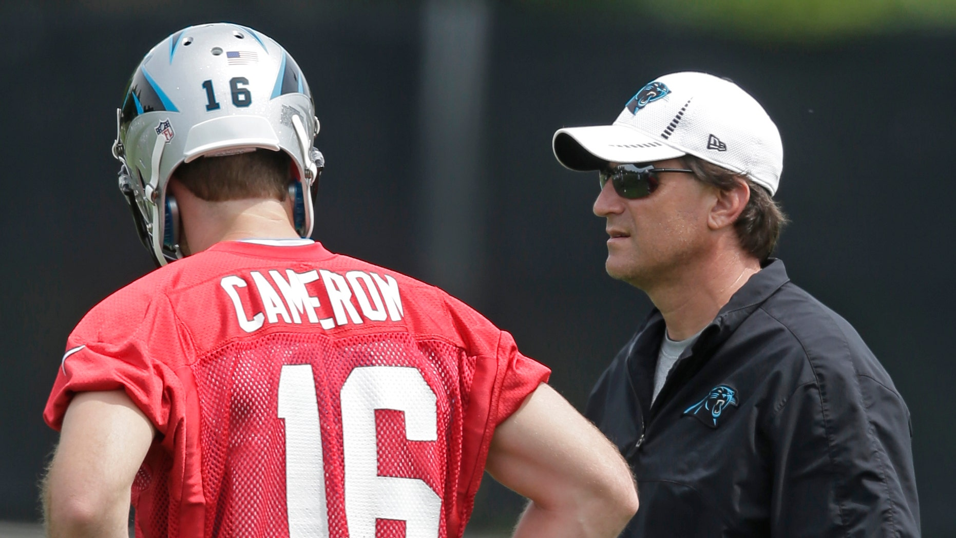 Carolina Panthers offensive coordinator Mike Shula, right, talks with quarterback Colby Cameron, left, during an NFL football rookie camp in Charlotte, N.C., Saturday, May 11, 2013. (AP Photo/Chuck Burton)