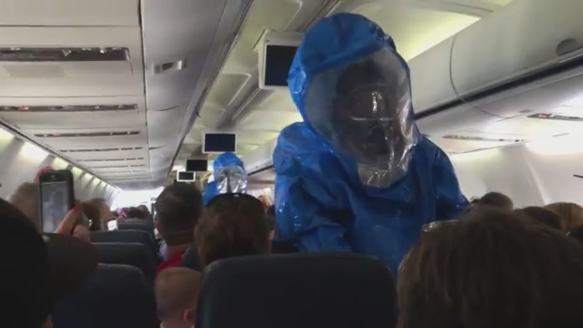 Emergency responders in hazmat suits on US Airways flight 845 from Philadelphia to Dominican Republic after a passenger caused a health scare.