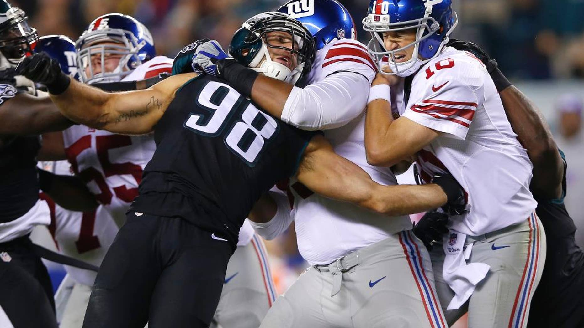 Philadelphia Eagles outside linebacker Connor Barwin (98) is held by New York Giants tackle Will Beatty, center left, as quarterback Eli Manning, center right, is hit by Eagles' Trent Cole, right, after throwing an incomplete pass during the second half of an NFL football game, Sunday, Oct. 12, 2014, in Philadelphia. (AP Photo/Michael Perez)