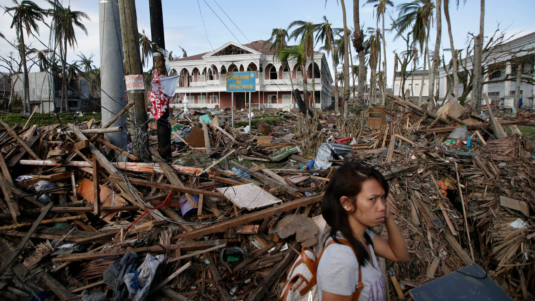 A typhoon survivor walks past the debris-littered Sto. Nino Shrine and Heritage Museum which used to house former Philippine First Lady Imelda Marcos' collection of art pieces from Philippine national artists Sunday Nov. 17, 2013 at  Tacloban city, Leyte province in central Philippines. Typhoon Haiyan, one of the most powerful typhoons ever recorded, slammed into central Philippine provinces Nov.8, leaving a wide swath of destruction and thousands of people dead.(AP Photo/Bullit Marquez)