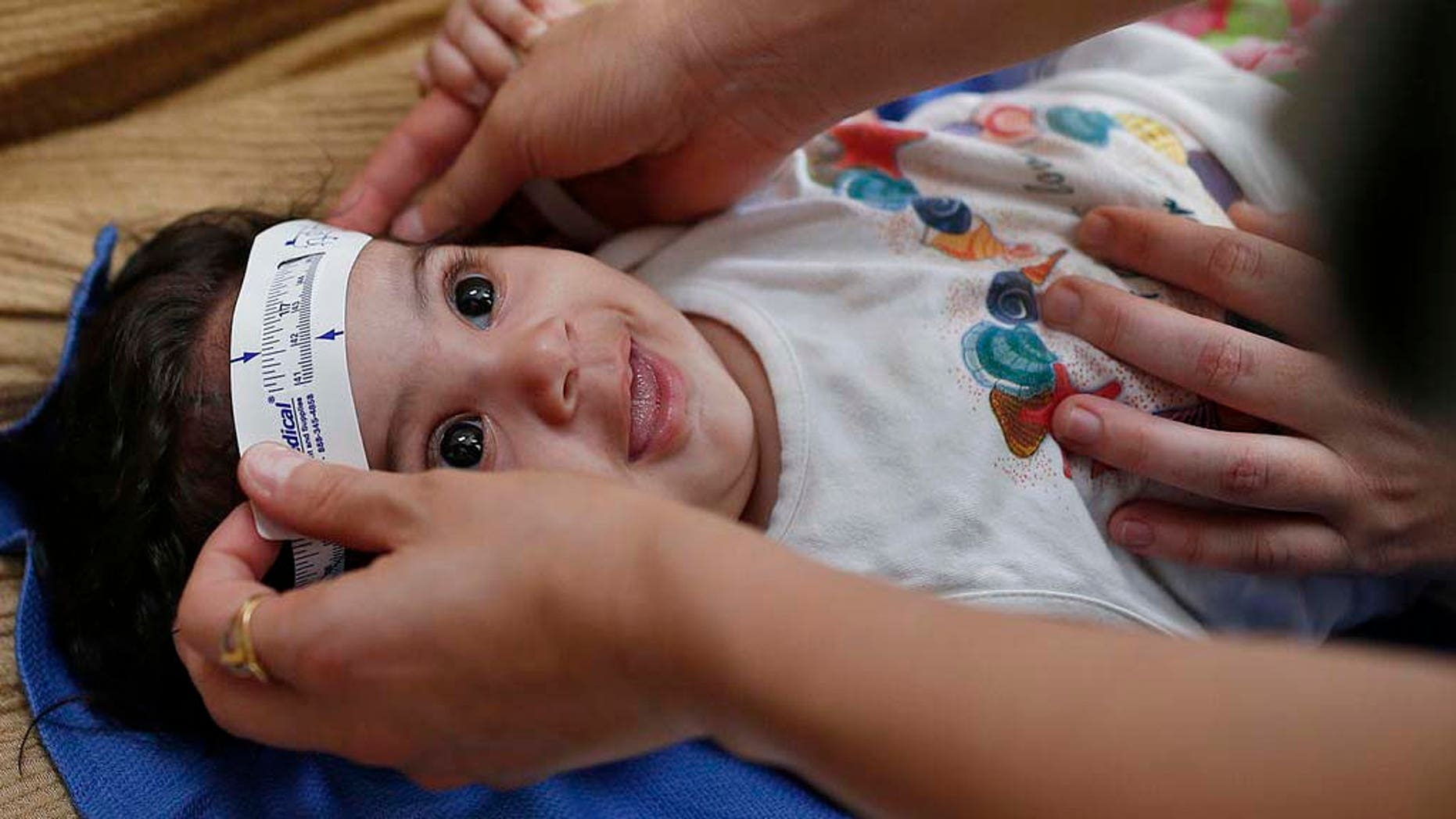 FILE - In this Wednesday, Feb. 24, 2016 file photo, 3-month-old Esther Kamilly has her head measured by Brazilian and U.S. health workers from the United States' Centers for Disease Control and Prevention (CDC) at her home in Joao Pessoa, Brazil, as part of a study on the Zika virus and the birth defect microcephaly. As the international epidemic of Zika has unfolded and led to devastating birth defects for at least 1,300 children in eight countries, an agonizing question has persisted: What is the chance that an infected pregnant woman will have a baby with these defects? (AP Photo/Andre Penner)