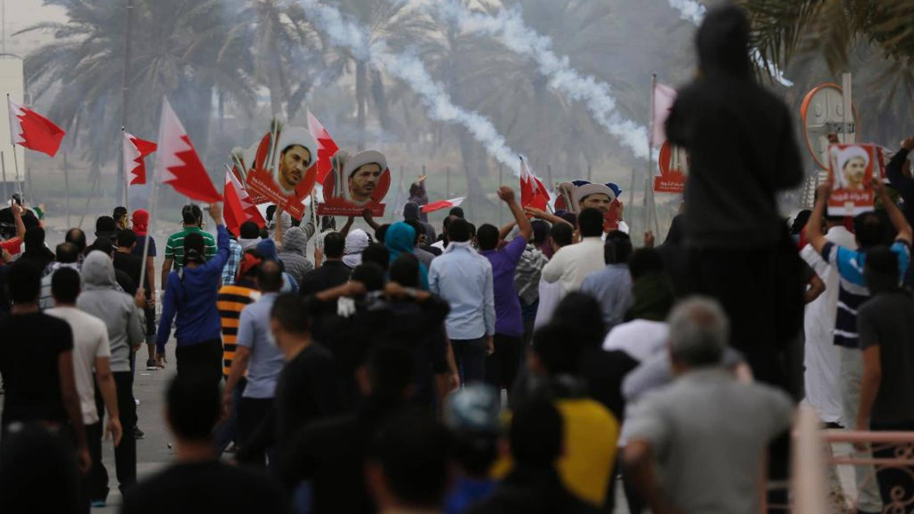 Riot police fire tear gas to disperse Bahraini anti-government protesters waving flags and carrying pictures of jailed Shiite cleric Sheikh Ali Salman, head of the largest opposition political society, Friday, Feb. 13, 2015, in the Manama suburb of Bilad al-Qadeem, Bahrain. Protest marches were held and clashes erupted in opposition areas nationwide Friday, where many shops stayed closed as part of a three-day general strike called by the February 14 opposition youth group before Saturday's fourth anniversary of Bahrain's pro-democracy uprising. (AP Photo/Hasan Jamali)