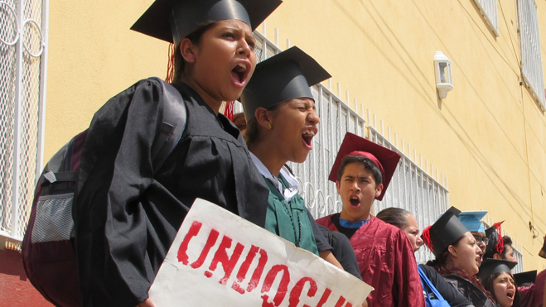 FILE - In this Sept. 20, 2013 file photo, wearing graduation-style caps and gowns, Mexican youth raised in the U.S, chant slogans outside a migrant shelter before crossing the international bridge from Nuevo Laredo, Mexico. A lawyer who traveled to the Texas-Mexico border with the 34 immigrants protesting U.S. immigration policies says 25 of the 26 remaining in federal custody have completed another step in their requests for asylum. (AP Photo/Christopher Sherman, File)