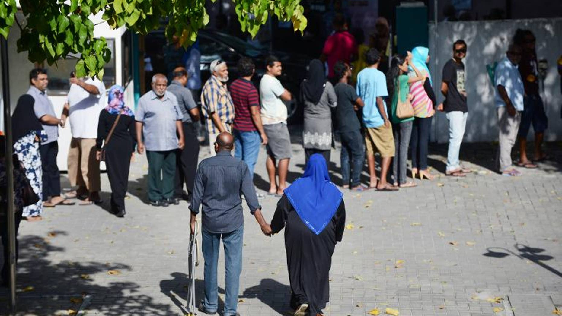 Two Maldivians walk towards the exit of a local polling station after having cast their vote in Male on September 7, 2013