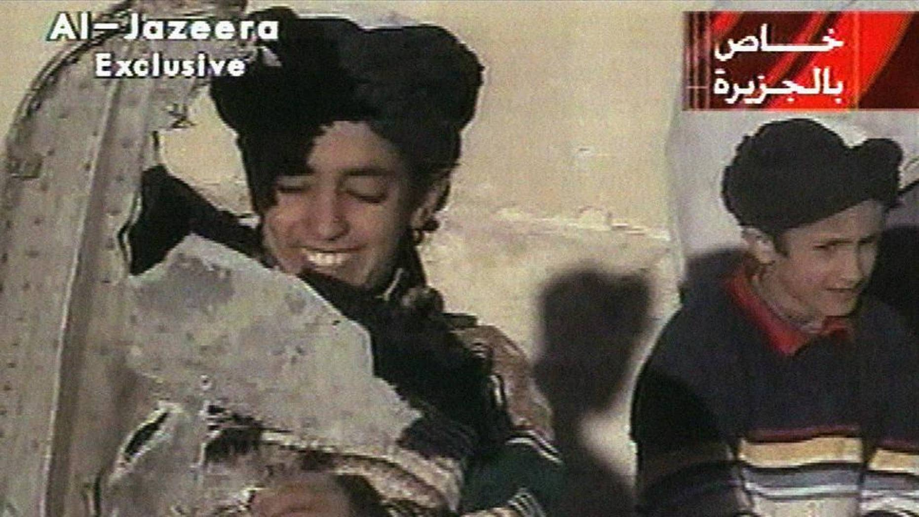 """In this image made from video broadcast by the Qatari-based satellite television station Al-Jazeera Wednesday, Nov. 7, 2001, a young boy, left, identified as Hamza bin Laden holds what the Taliban says is a piece of U.S. helicopter wreckage in Ghazni, Afghanistan on Monday, Nov. 5, 2001. The Obama administration has announced terrorism-related sanctions against a son of Sept. 11 mastermind Osama bin Laden. The State Department says Hamza bin Laden has been """"determined to have committed, or pose a serious risk of committing, acts of terrorism that threaten the security of U.S. nationals or the national security.""""  (AP Photo/Al-Jazeera via APTN) ** TV OUT **"""