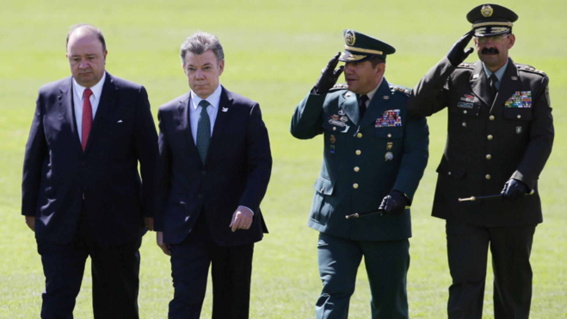 De izquierda a derecha, el ministro colombiano de Defensa, Luis Carlos Villegas; el presidente, Juan Manuel Santos; el comandante de las Fuerzas Armadas Juan Pablo Rodríguez y el jefe de la policía colombiana, Rodolfo Palomino, pasan revista a las tropas durante una ceremonia militar en Bogotá, Colombia, el 9 de julio de 2015. (AP Foto/Fernando Vergara)