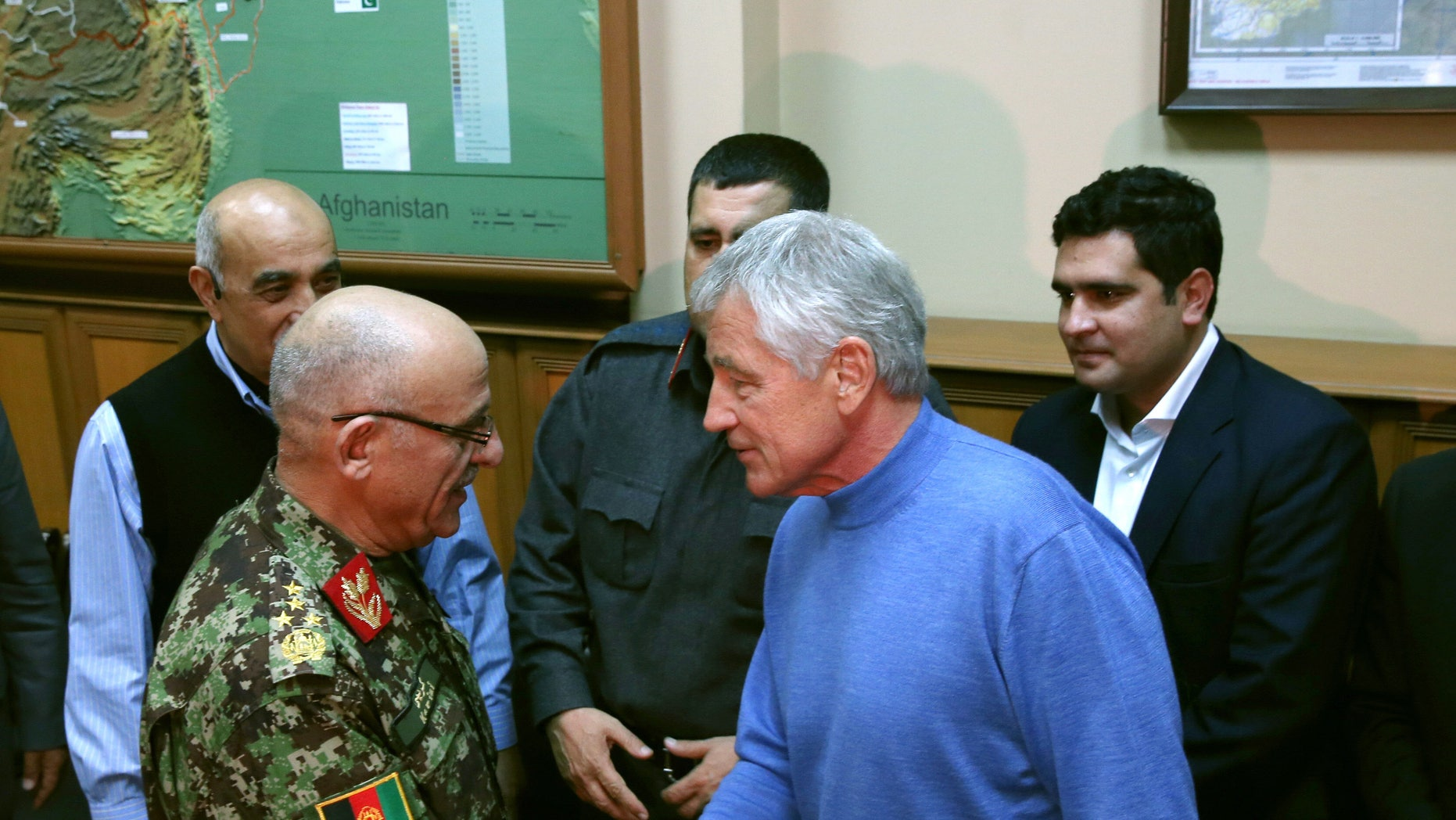 U.S. Secretary of Defense Chuck Hagel, right, shakes hands with Afghan Gen. Sher Mohammad Karimi, left, during a meeting at the International Security Assistance Force Headquarters (ISAF) on Saturday, Dec. 7, 2013 in Kabul, Afghanistan. Secretary Hagel made a stop in Afghanistan during his six-day trip to the Middle East.  (AP Photo/Mark Wilson, Pool)