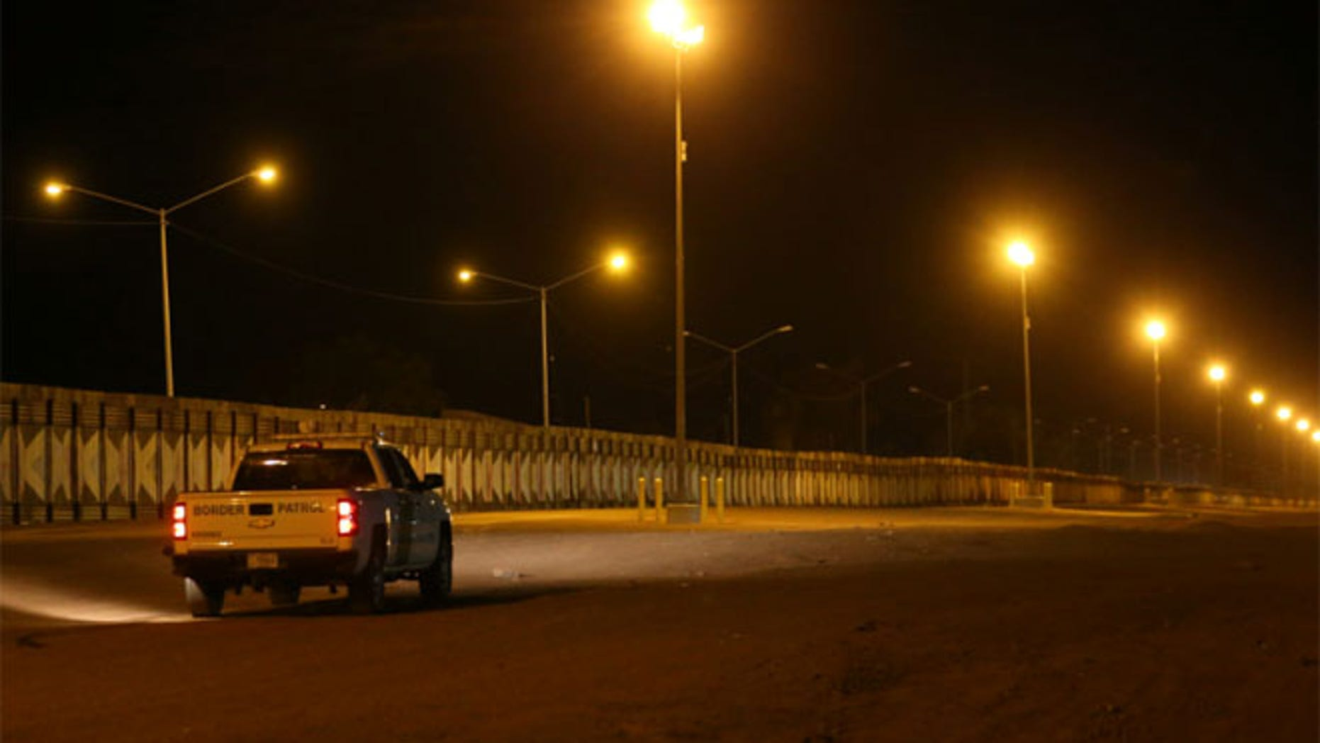 U.S. border patrol agents patrol at night along the border wall next to Mexico in Calexico, California