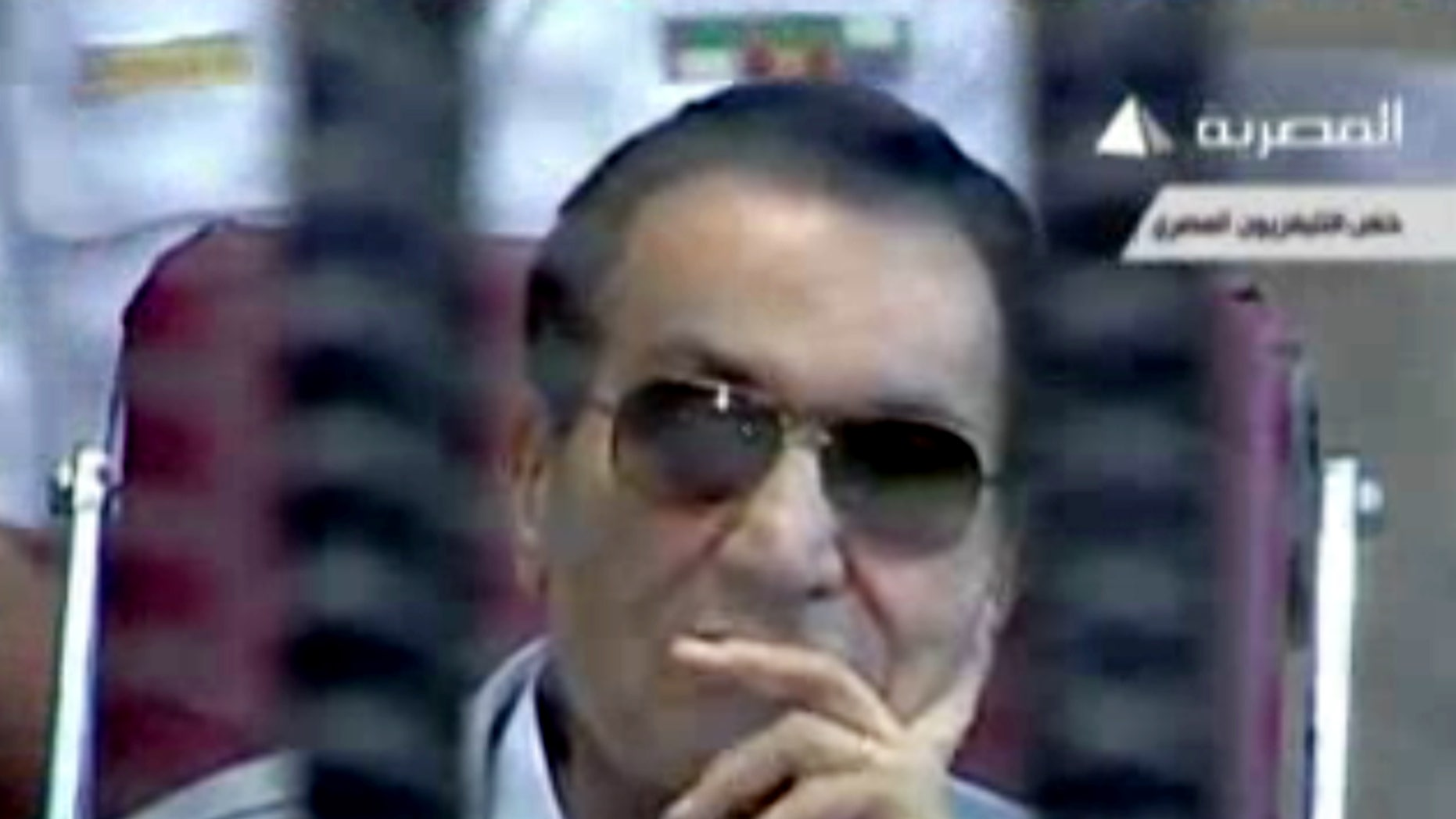 This image made from video broadcast on Egyptian state television shows former President Hosni Mubarak inside the defendant's cage in a courtroom in Cairo, Egypt, Saturday, May 11, 2013. The retrial of former Egyptian President Hosni Mubarak resumed Saturday, with prosecutors requesting to present new evidence from a fact-finding commission's report that claims the ex-leader had full knowledge of the extent of the violence used against protesters. (AP Photo/Egyptian State Television via AP video)
