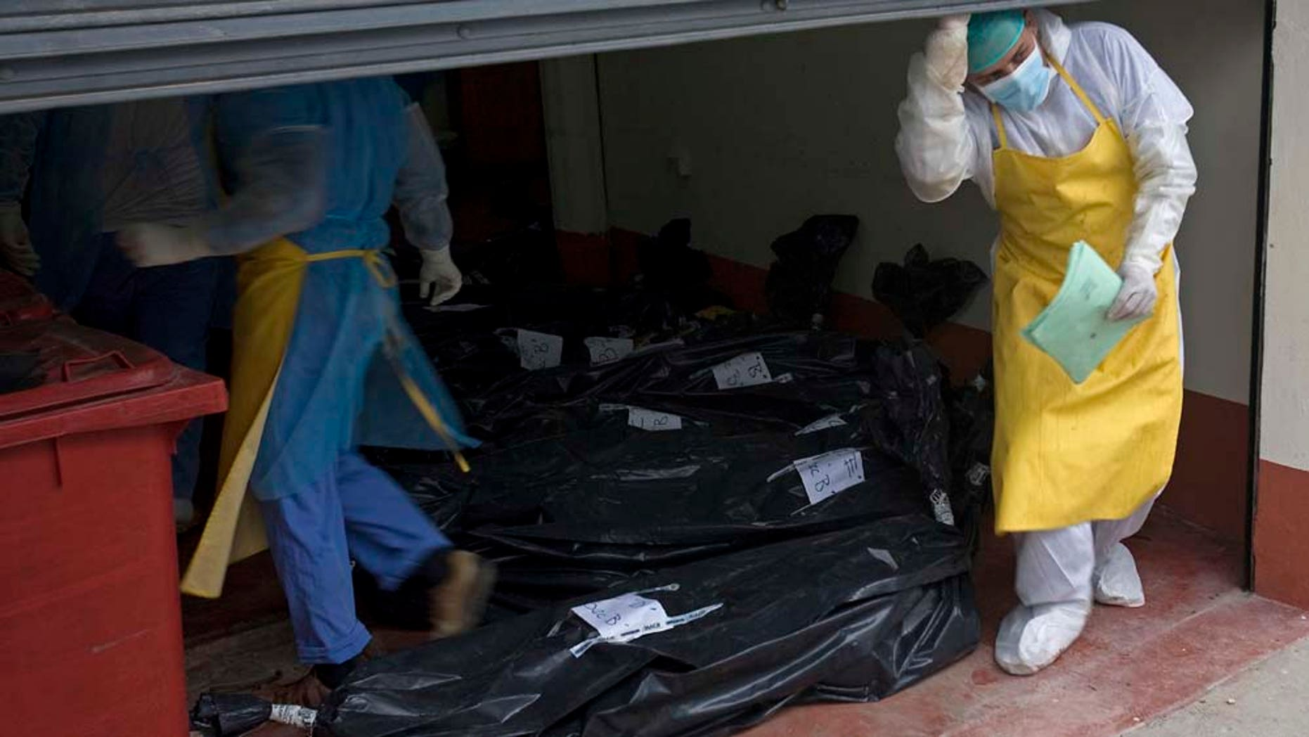 Morgue employees take in the bodies that were found on a ranch in northern Guatemala, at the local morgue in San Benito, Guatemala, Monday, May 16, 2011. Initial reports said assailants killed Sunday at least 29 people, but Monday the death toll confirmed decreased to 27 persons. Guatemalan authorities on Monday blamed the massacre on the Mexican drug cartel the Zetas. (AP Photo/Moises Castillo)