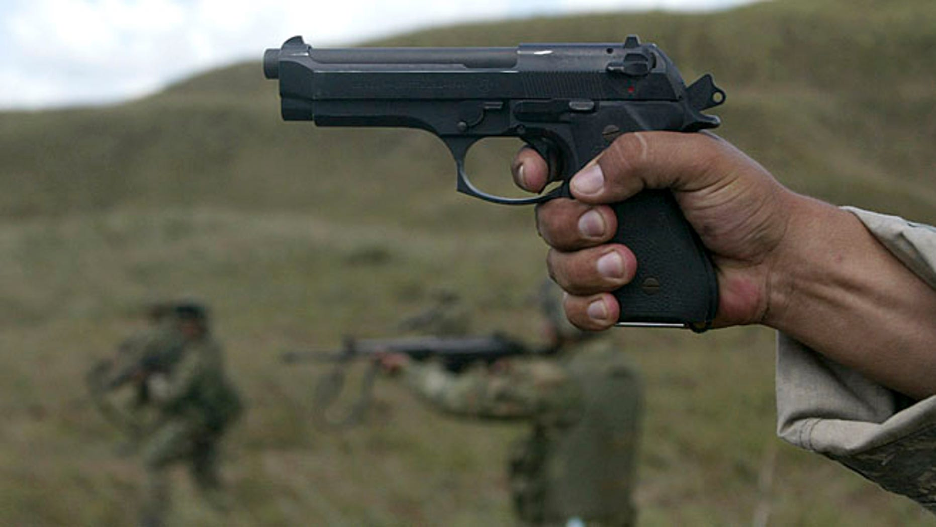 FILE: 2007: A U.S. army instructor fires with Colombian soldiers during a combat exercise in a southern Colombian.