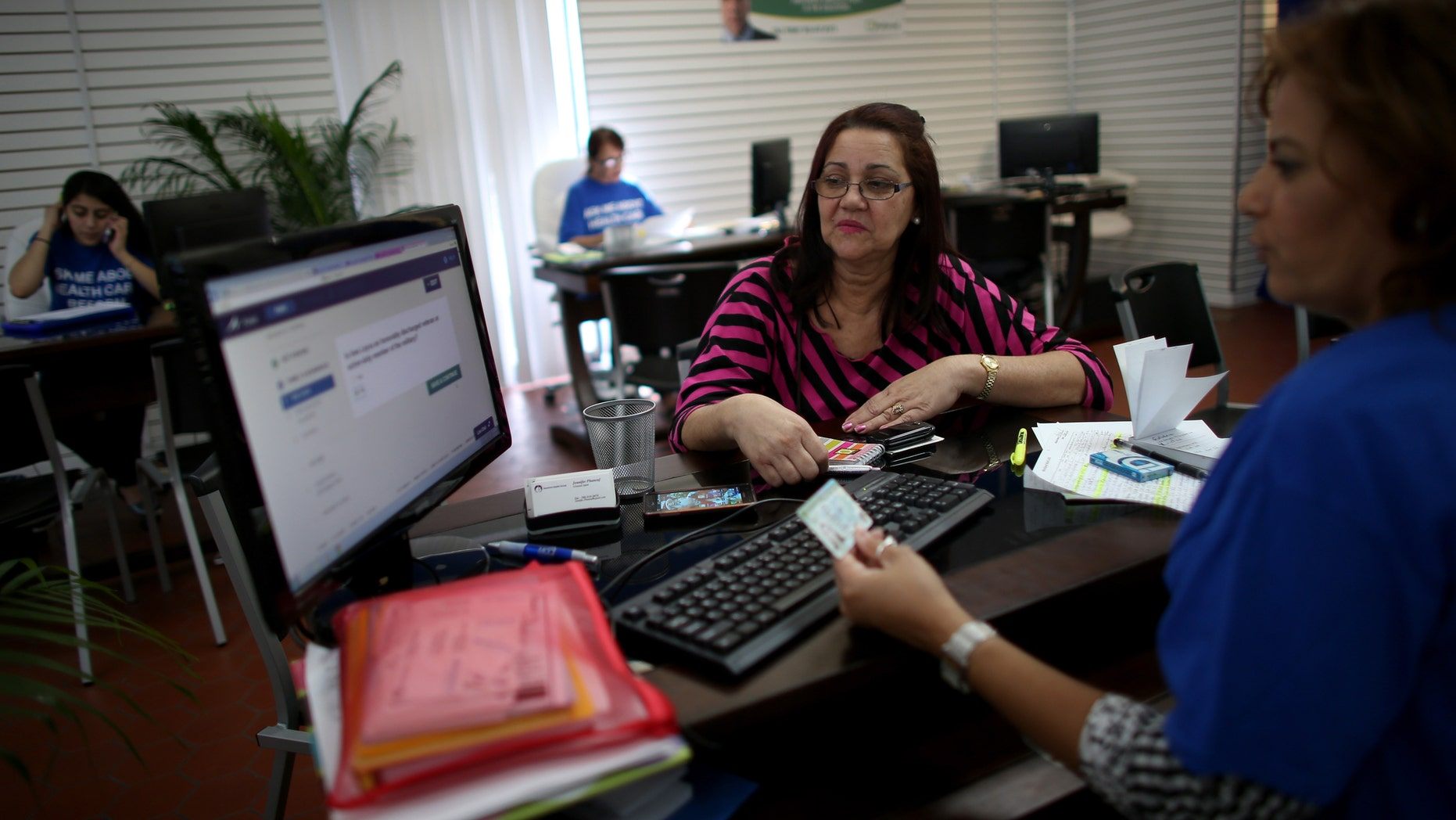 HIALEAH, FL - NOVEMBER 14:  Ines Leyva works with Marlene Portuondo, an insurance agent with Sunshine Life and Health Advisors, as she looks to purchase an insurance policy under the Affordable Care Act at the store setup in the Westland Mall on November 14, 2013 in Hialeah, Florida. As the insurance agents continue to help people purchase and understand the policies offered under the Affordable Care Act, U.S. President Barack Obama announced that Americans who have had their health insurance plans canceled because of the Affordable Care Act can keep those plans for another year if they wish to.  (Photo by Joe Raedle/Getty Images)