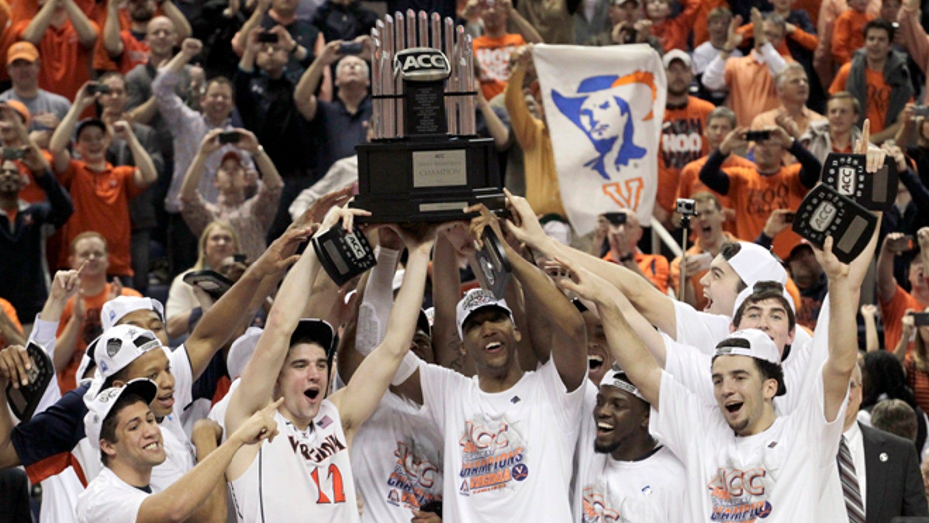 Virginia players celebrate with the trophy after defeating Duke in an NCAA college basketball game in the championship of the Atlantic Coast Conference tournament in Greensboro, N.C., Sunday, March 16, 2014. Virginia won 72-63. (AP Photo/Bob Leverone)